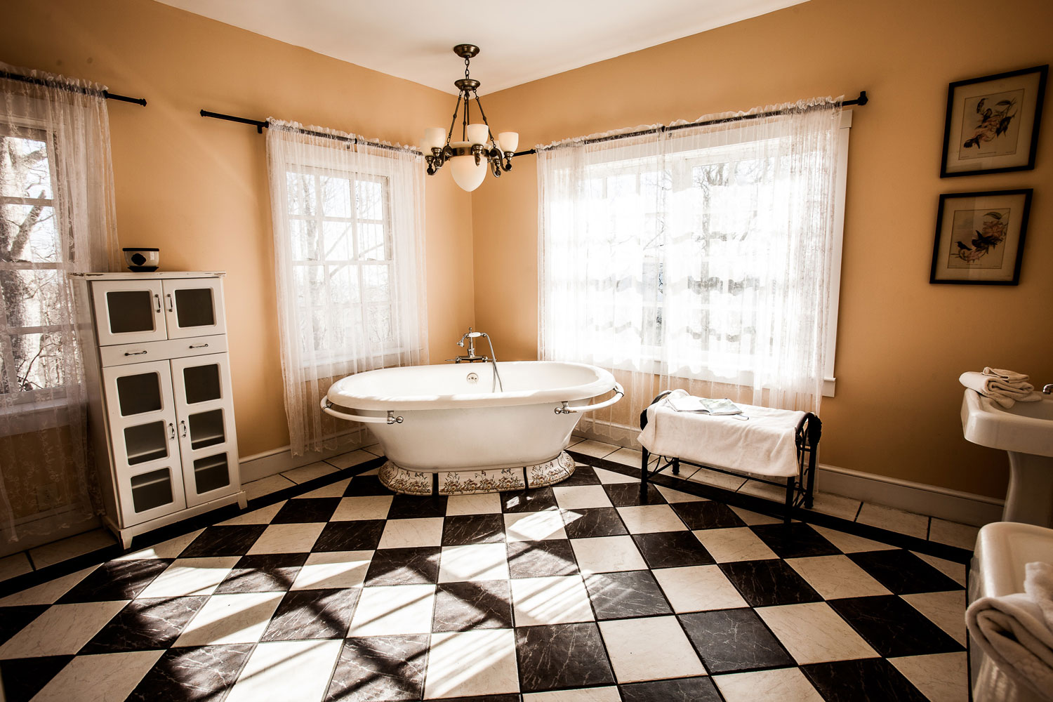 A soaking bathtub surrounded by natural light, large windows, and a hanging chandelier. His and hers sinks are against the opposite wall of the bathtub. This bathroom is part of the Versace suite.