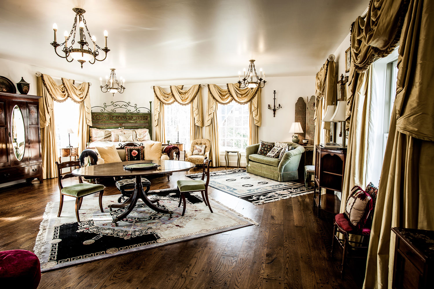 A spacious and immaculate bedroom with curtain draped windows facing every direction. A dining table and accompanying chairs atop an antique rug sit in front of the Queen sized bed. Three hanging chandeliers, plush chairs, and old English details adorn every corner of the room.