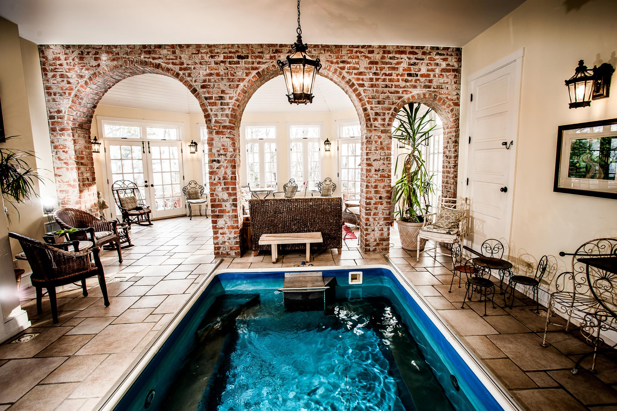 An endless swimming pool behind the sun room with cafe tables and chairs on either side of the pool.