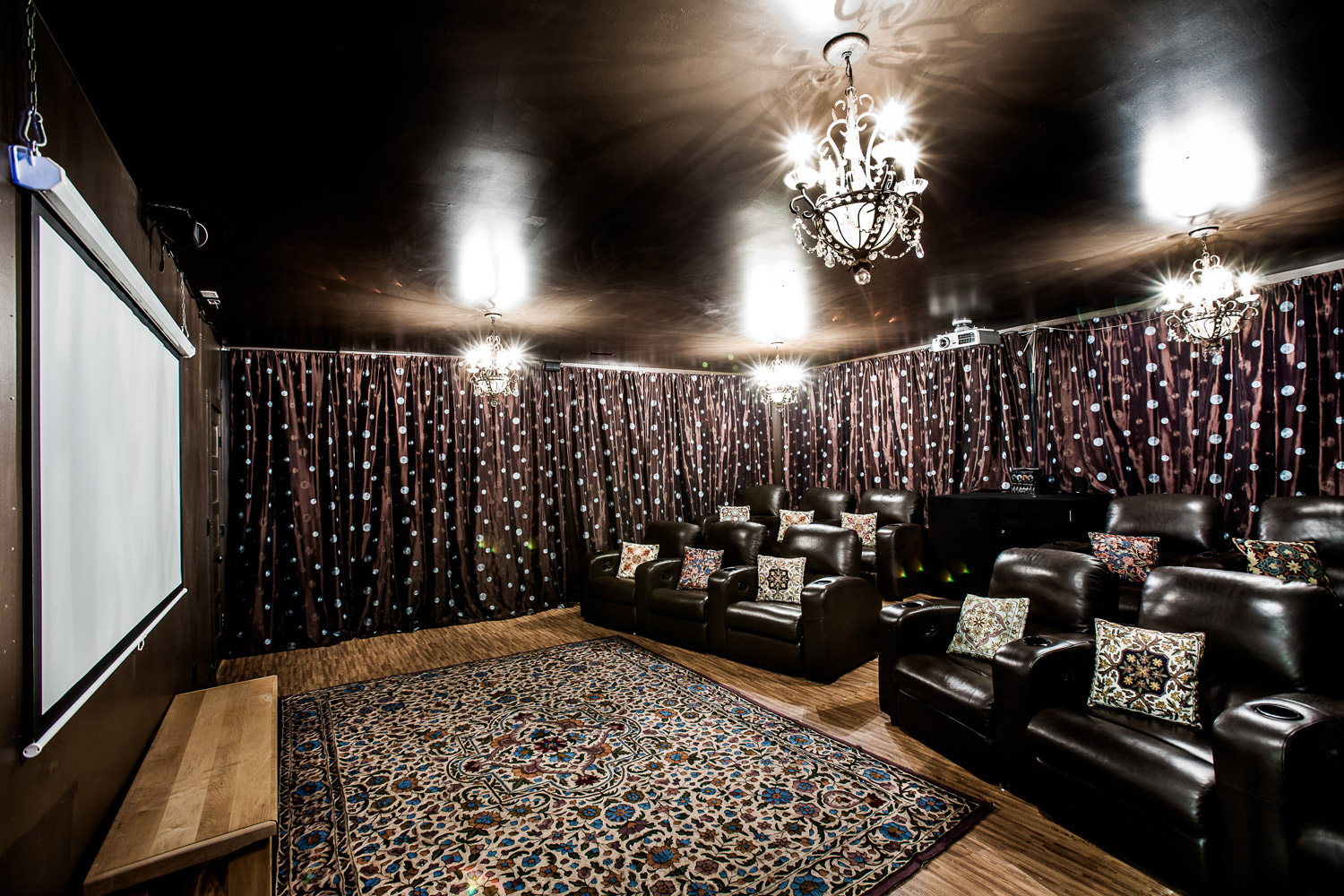 In-home movie theater with reclining leather seats and a surround sound stereo system