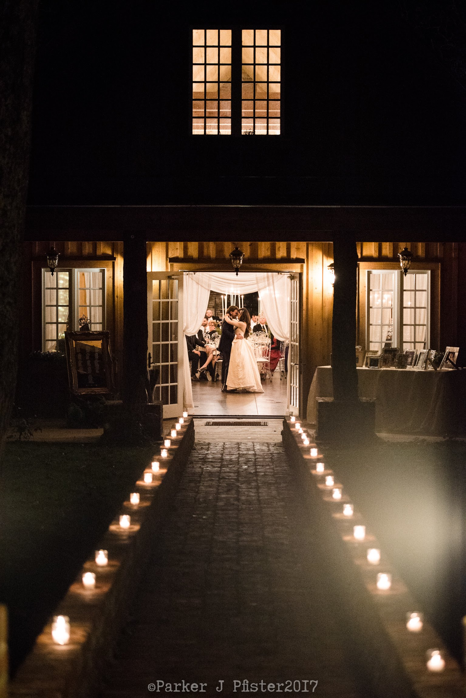 Bride and groom dancing in the reception hall, illuminated by candlelights
