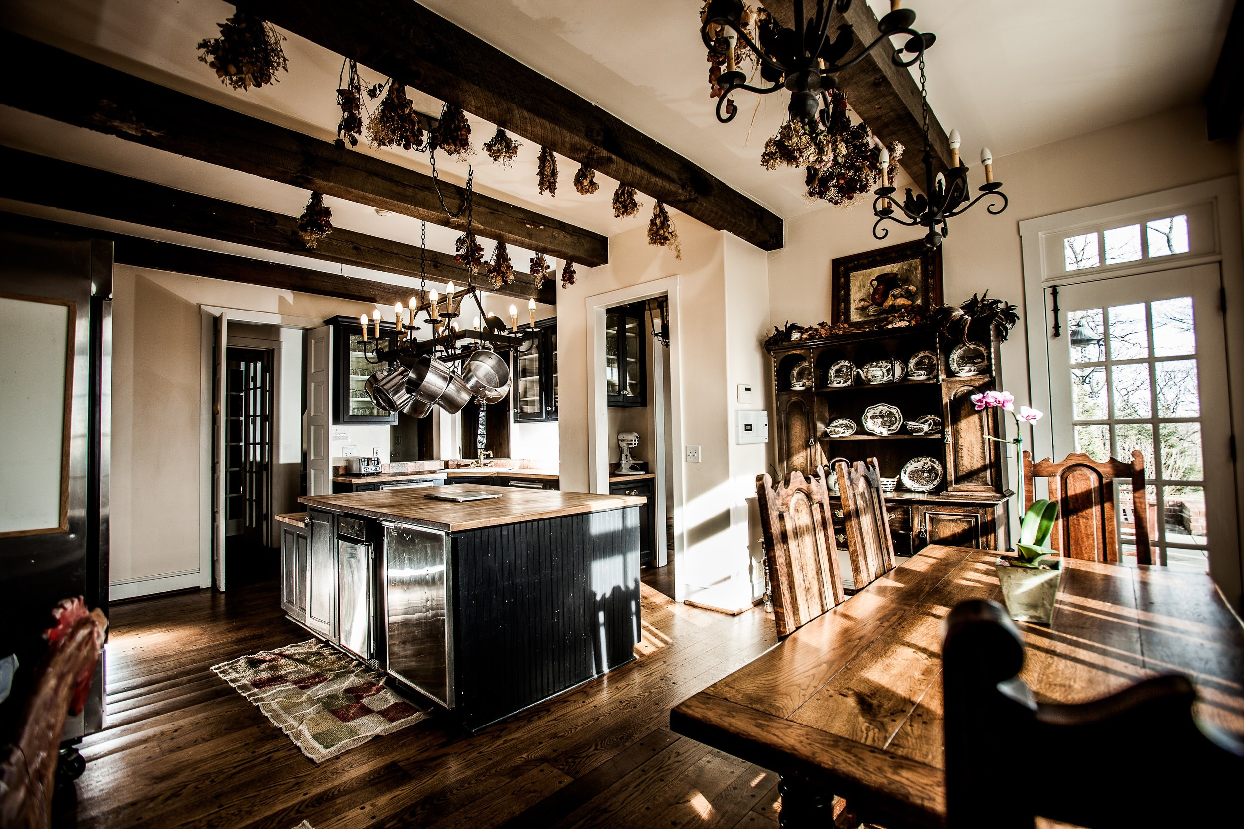A large, sun soaked kitchen with an island and wooden breakfast table. Dried bouquets from brides hangs from the ceiling. The kitchen has an industrial fridge, stove, and other kitchen appliances.