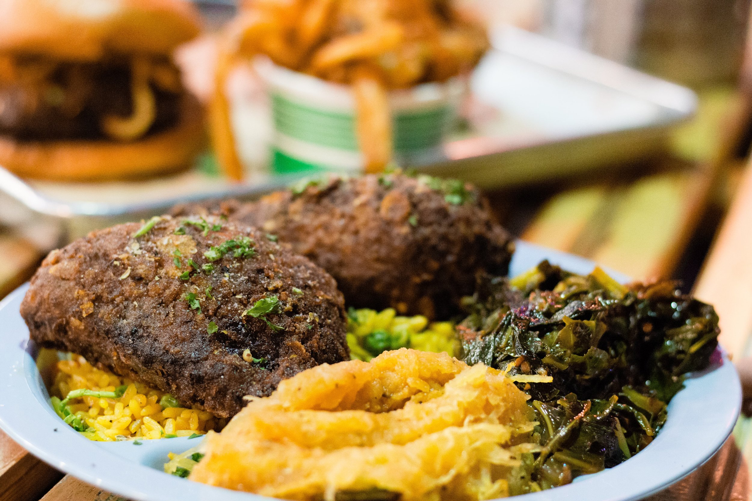 Spicy fried chicken served with sweet potatoes, collard greens, and South African yellow rice