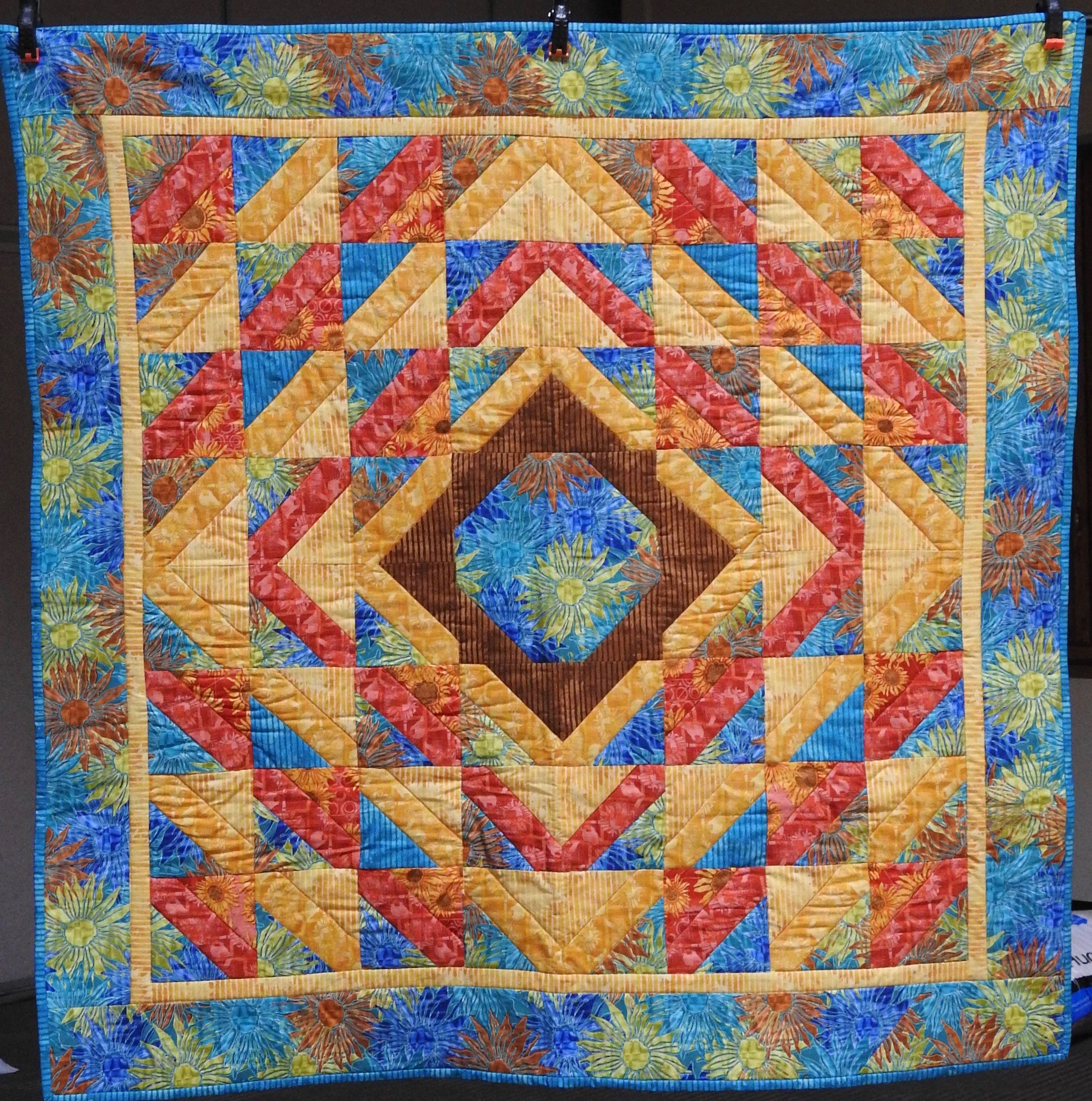 Southern Sunset, Pieced by Jean Mann Graber, Custom Machine Quilted, donated by The Cal Graber Family, 49 x 49""