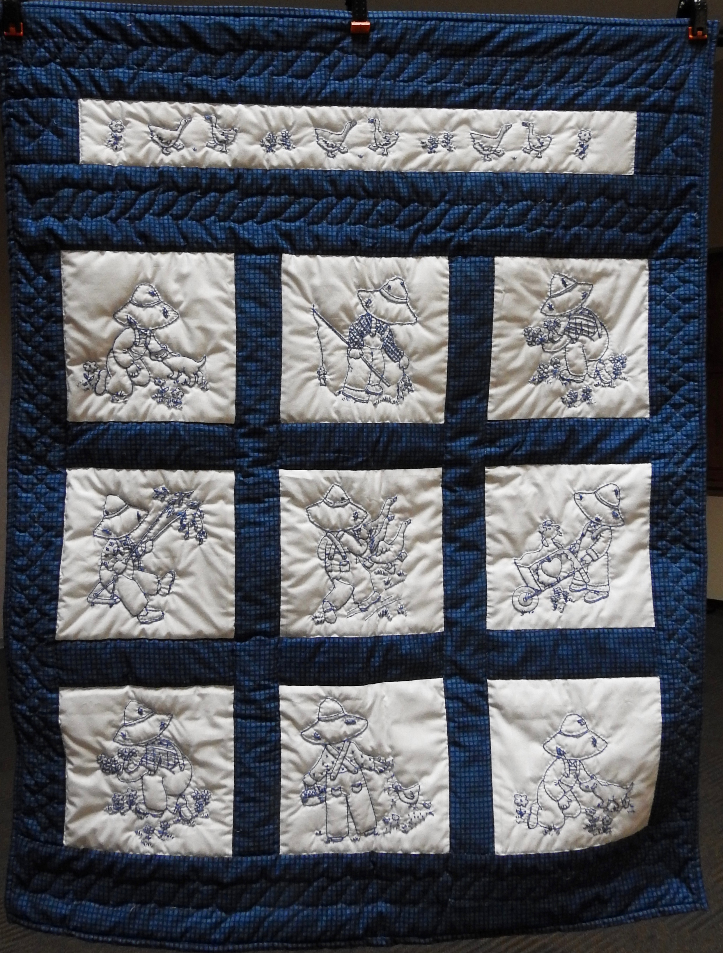 Overall Sam in Blue, Pieced & Embroidered, Hand Quilted by Susie Schlabach, donated Anonymously, 37 x 46