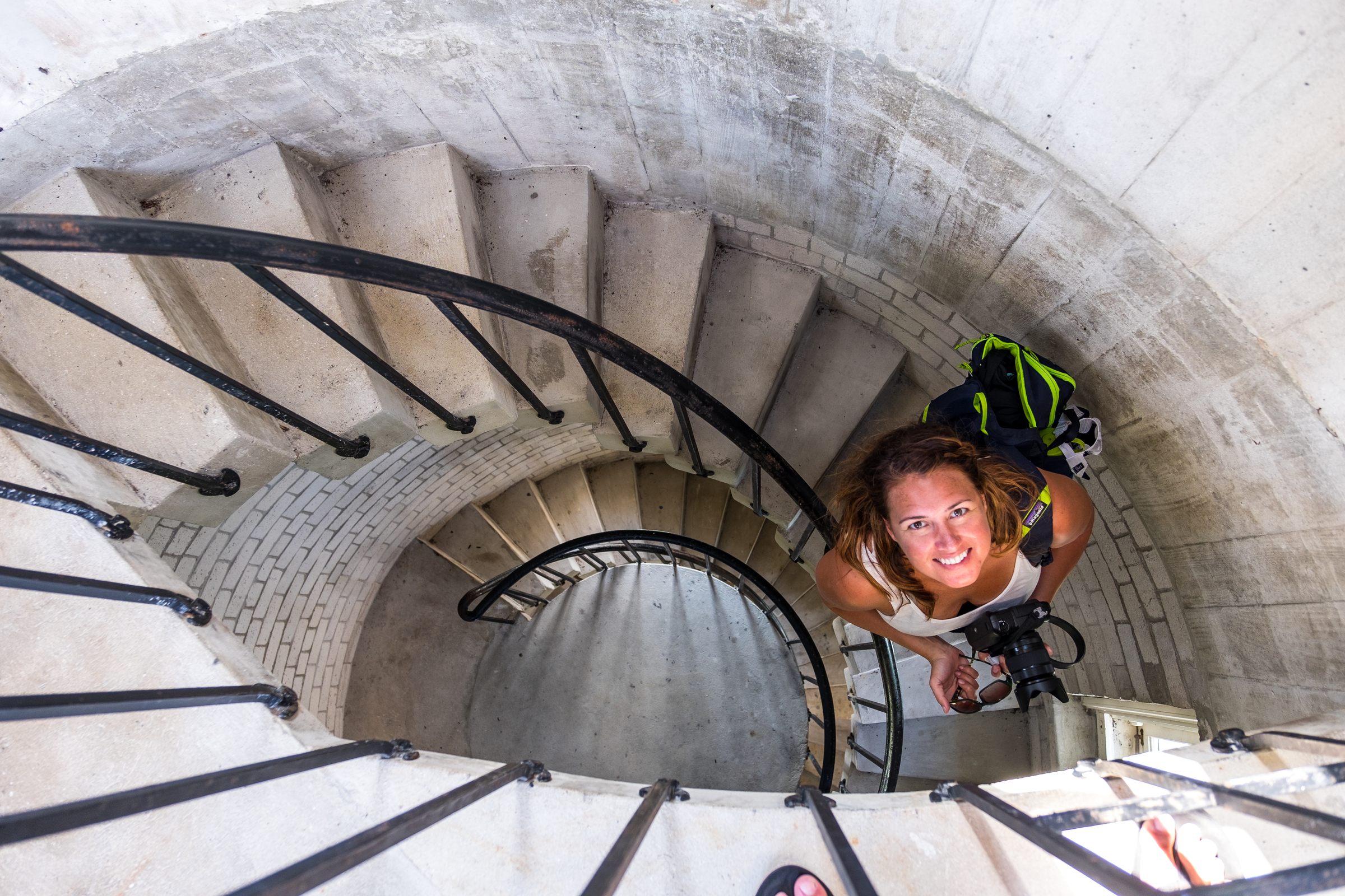 Stef climbs down the circular stairs of the lighthouse.