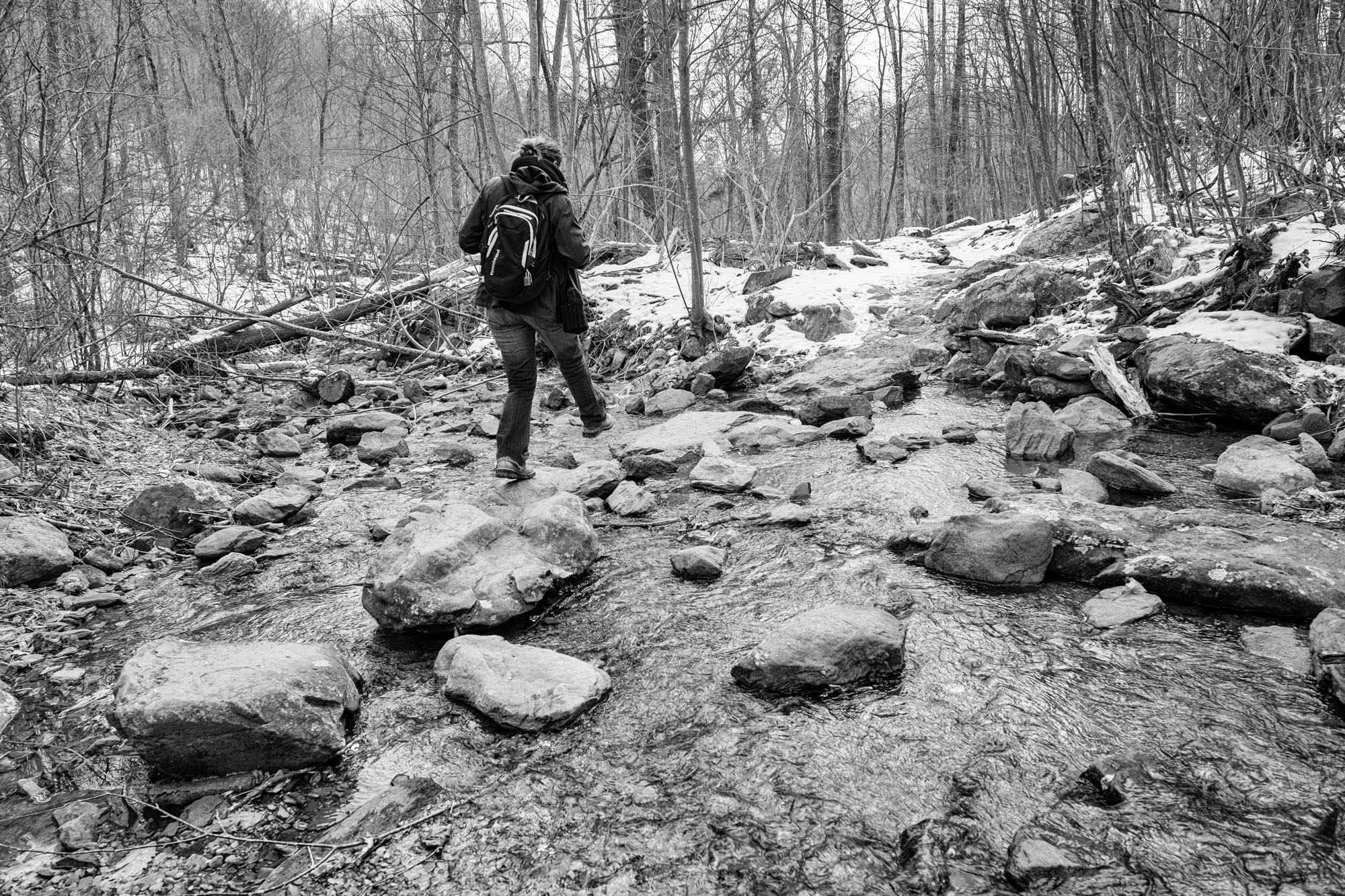 Stef steps from rock to rock on the way to Dark Hollow Falls.