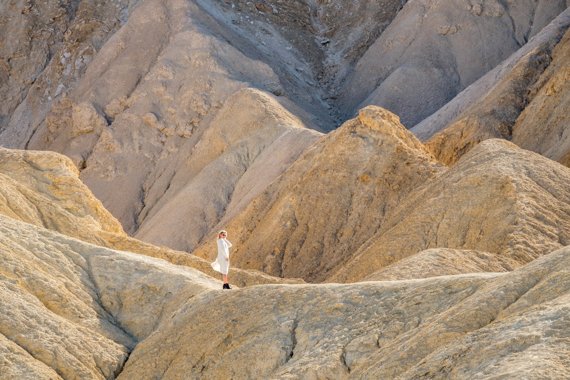 A women in a white dress walks the crazy formations just down the road from Zabriskie Point.
