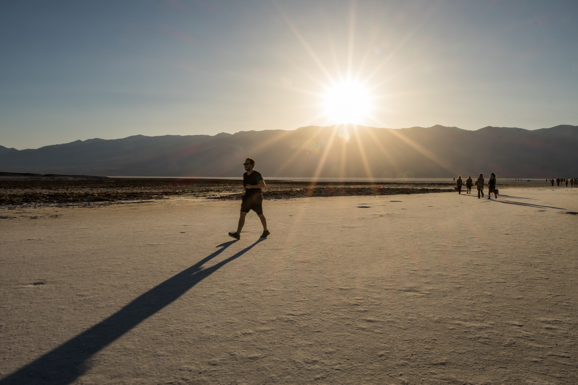 Tourists walking back from the middle of Badwater Basin as the sun sinks low.
