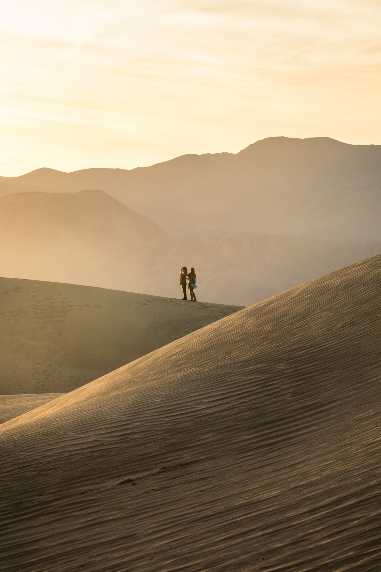 A special moment between two friends as the sun sets at Mesquite Sand Dunes.