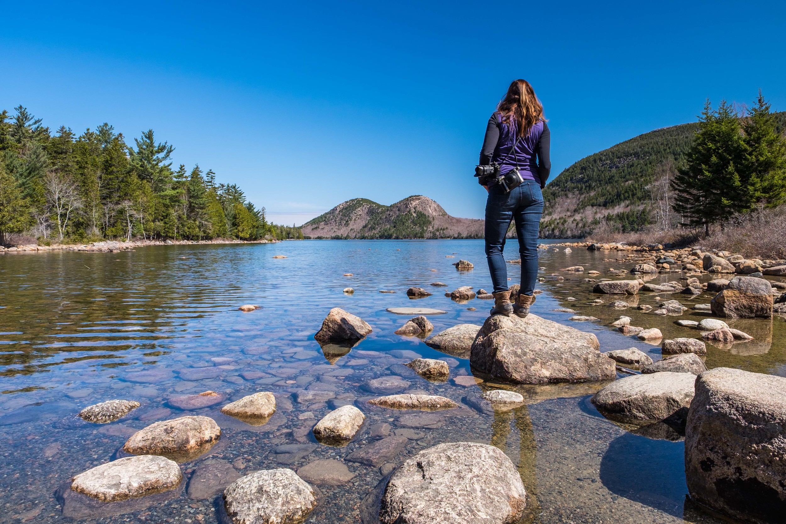 """Stef hangs out at the start of the Jordon Pond Shore Trail, with a view of """"The Bubbles"""" in the background."""