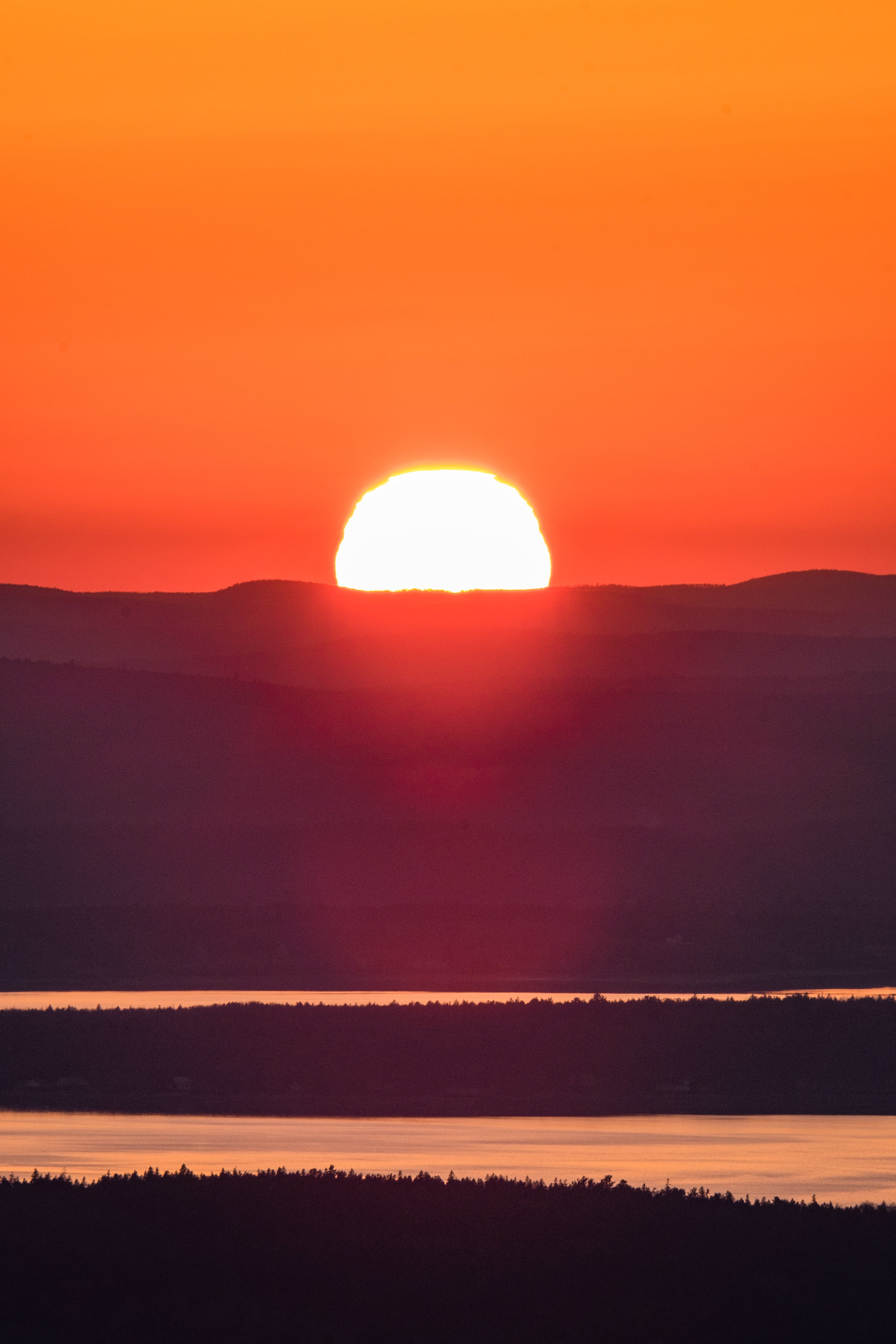 The sun sets as seen from Cadillac Mountain at Acadia National Park in Maine.
