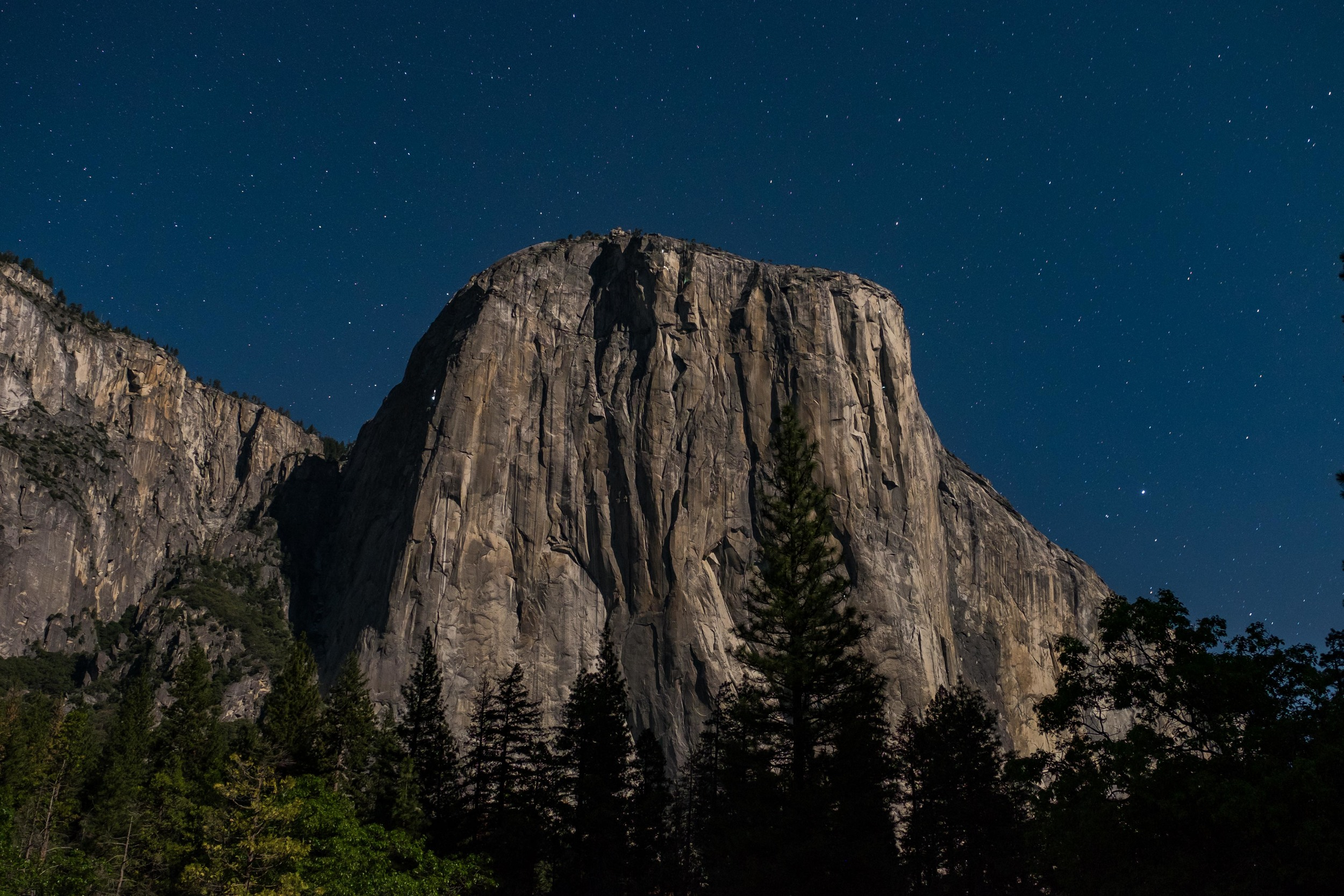 Yosemite's El Capitan at night. If you look closely, you can see climbers bivied up (i.e., sleeping in suspended sleep compartments) on the sheer face of the rock formation illuminated by small lanterns.