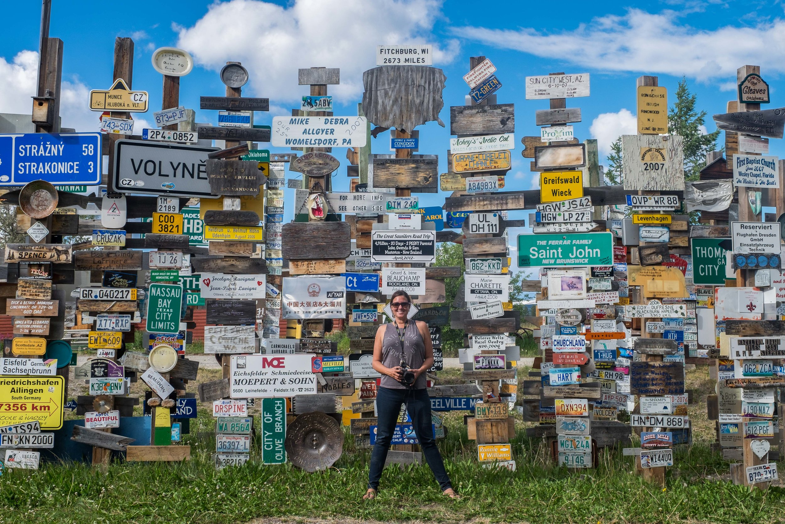 Stef is dwarfed beneath a collection of some 30,000 road signs that can be found at the Sign Post Forest in the Watson Lake area of the Yukon Territory.