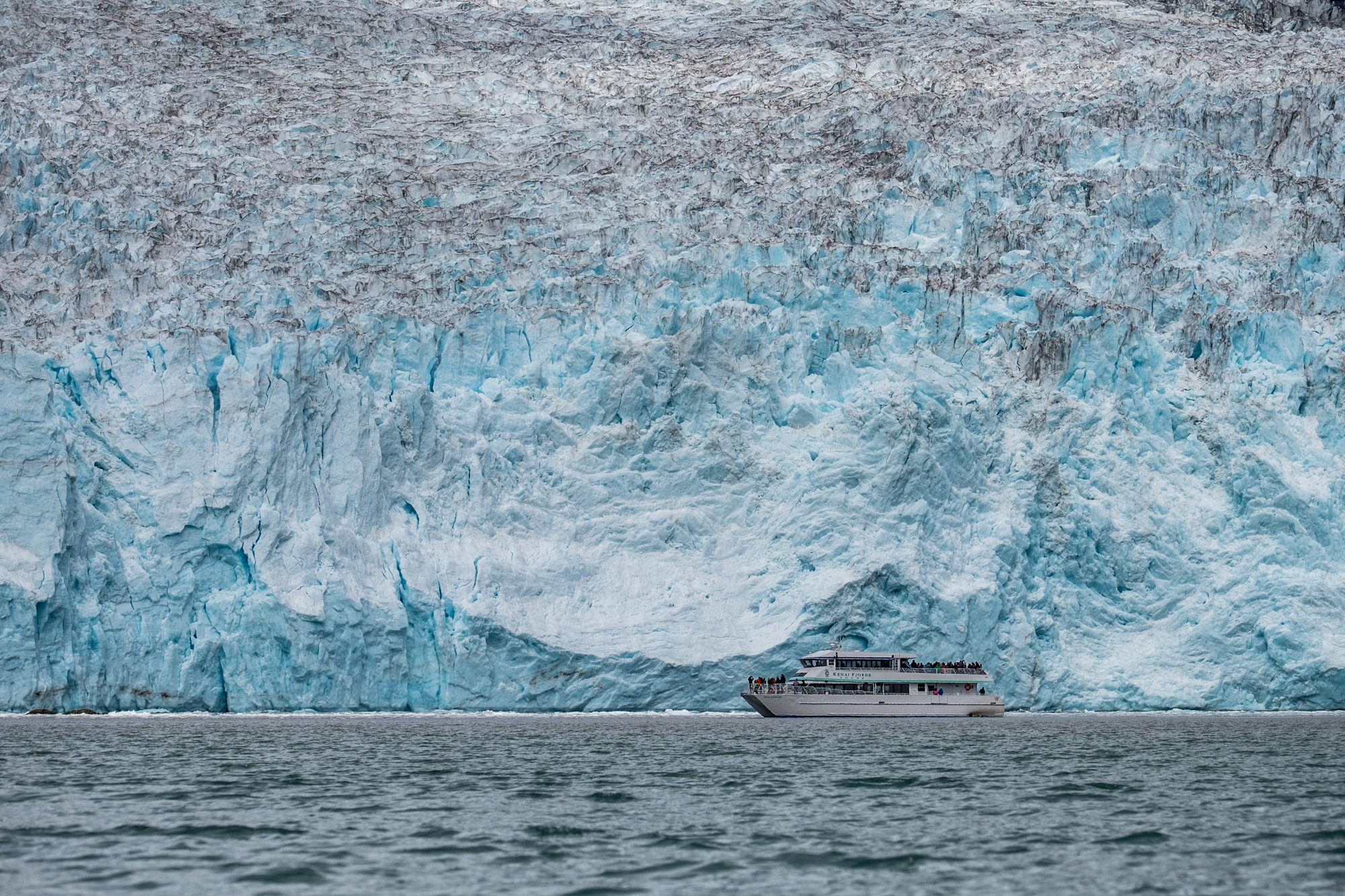 A cruise boat is dwarfed by the massive glacier.