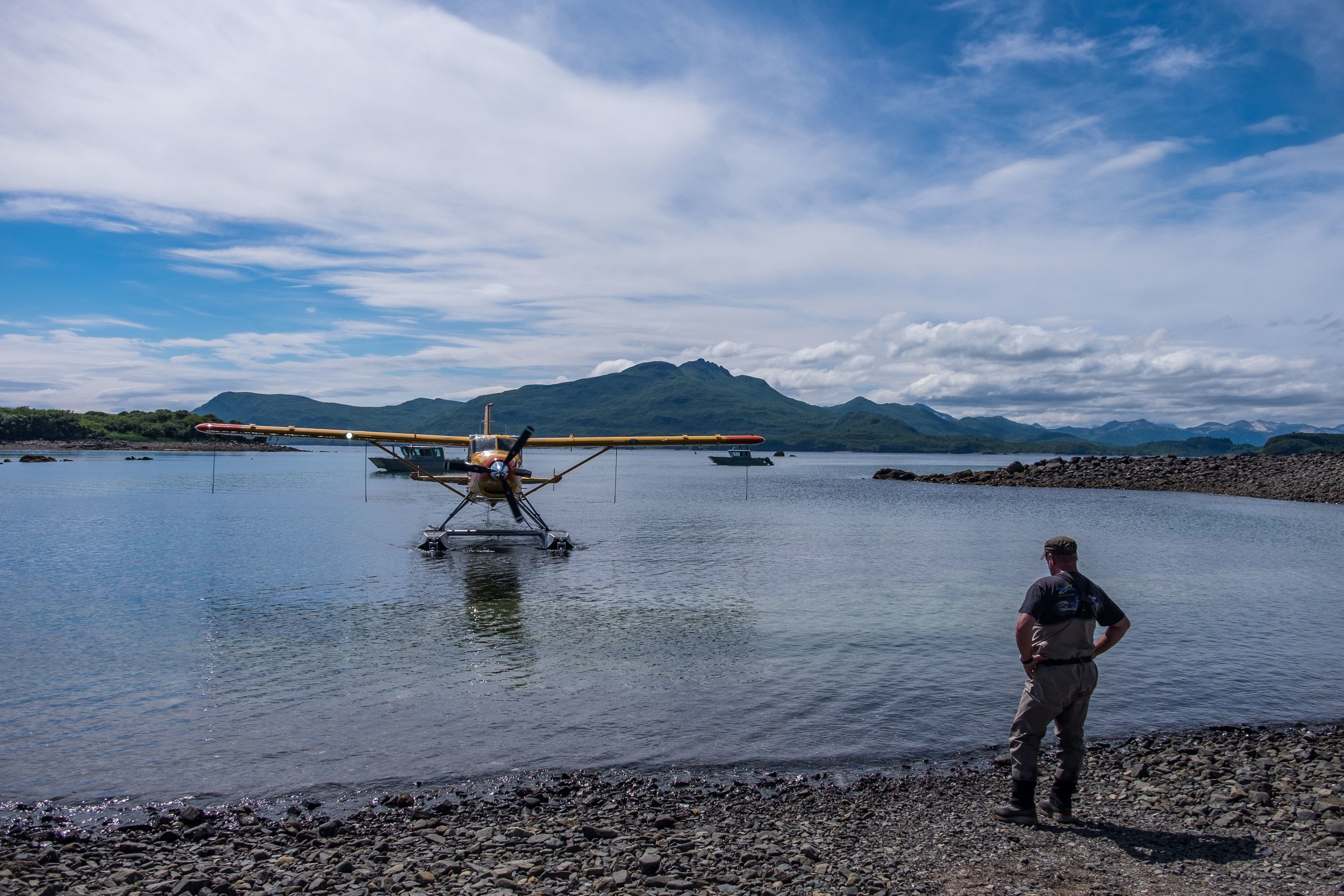 Perry Mollan, manager and bear naturalist at the Katmai Wilderness Lodge works with the crew at Andrews Airways to offload guests and supplies in the harbor outside of the lodge.