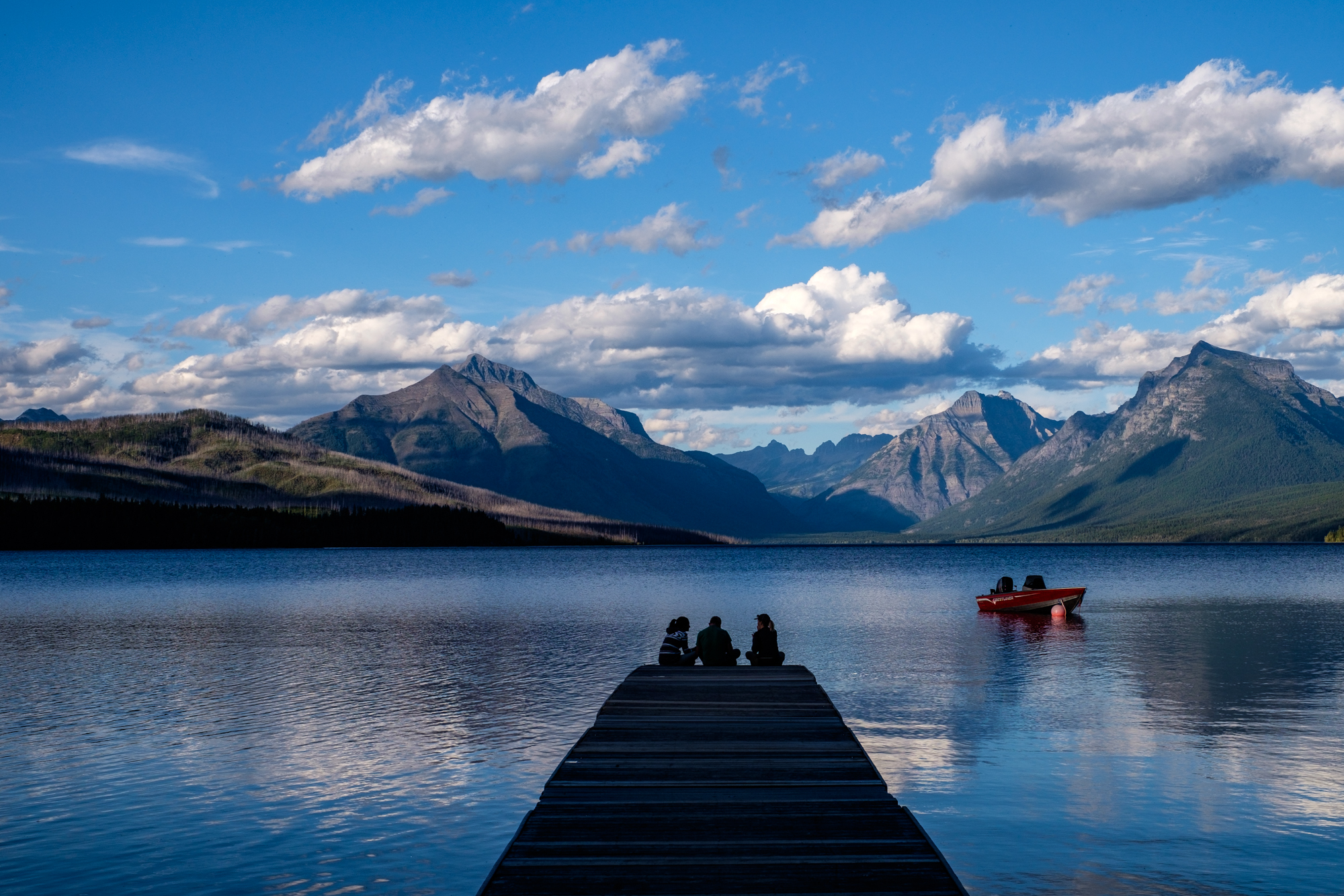 Friends gather to take in the views on a dock at McDonald Lake, the largest lake in the park.