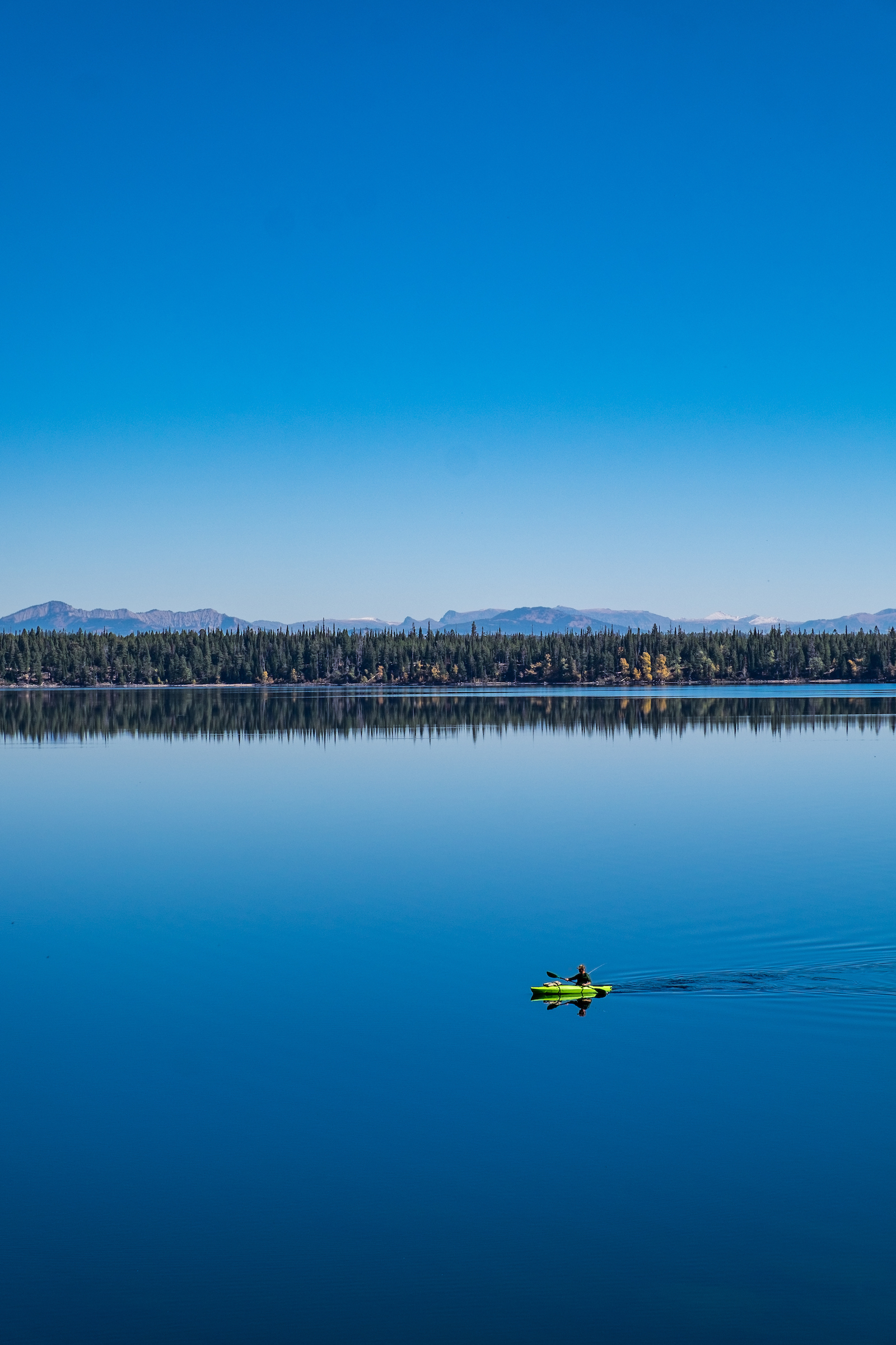 A paddler glides on the still waters of Jenny Lake.