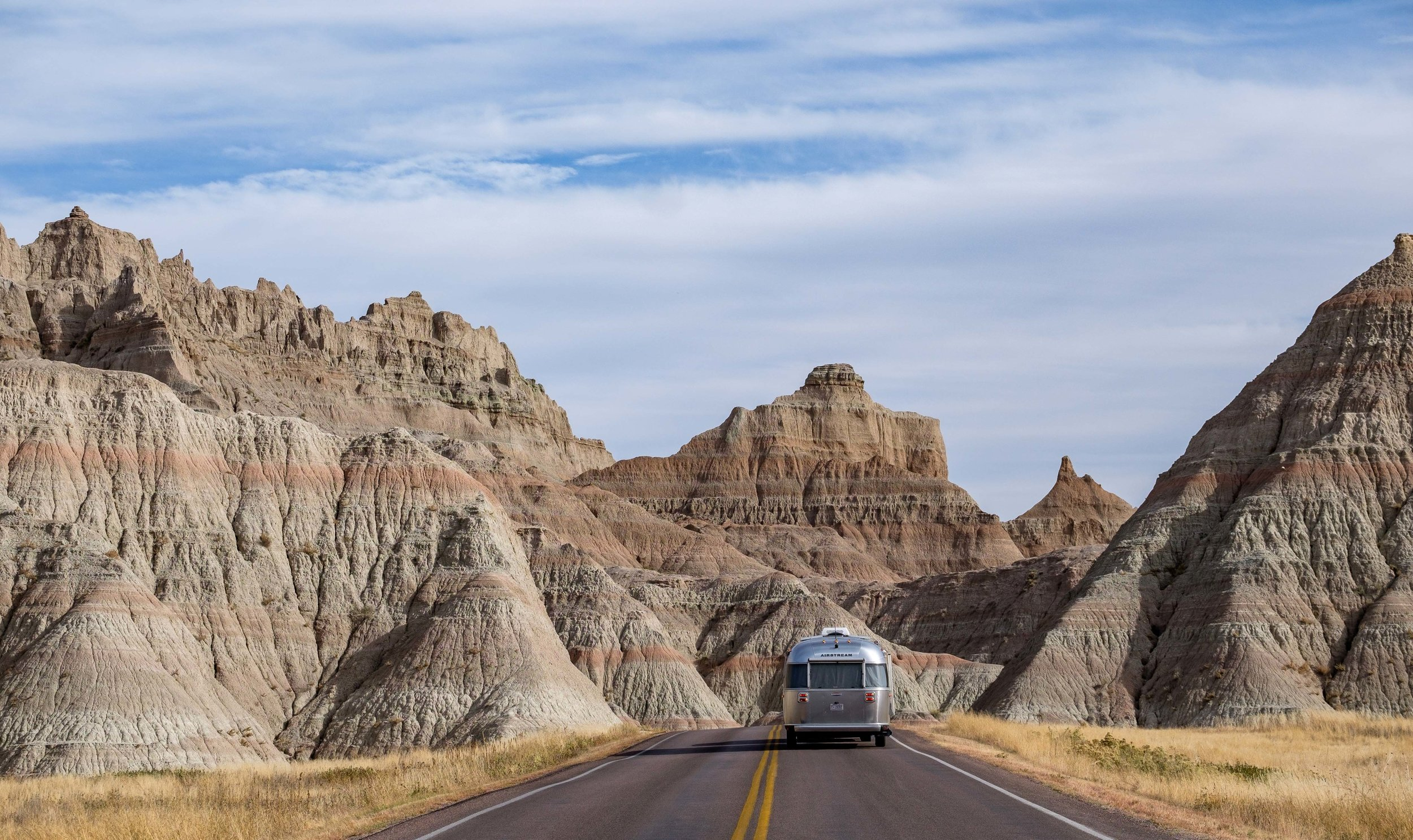 Wally the Airstream cradled by a wall of badland formations on Badlands Loop Road.