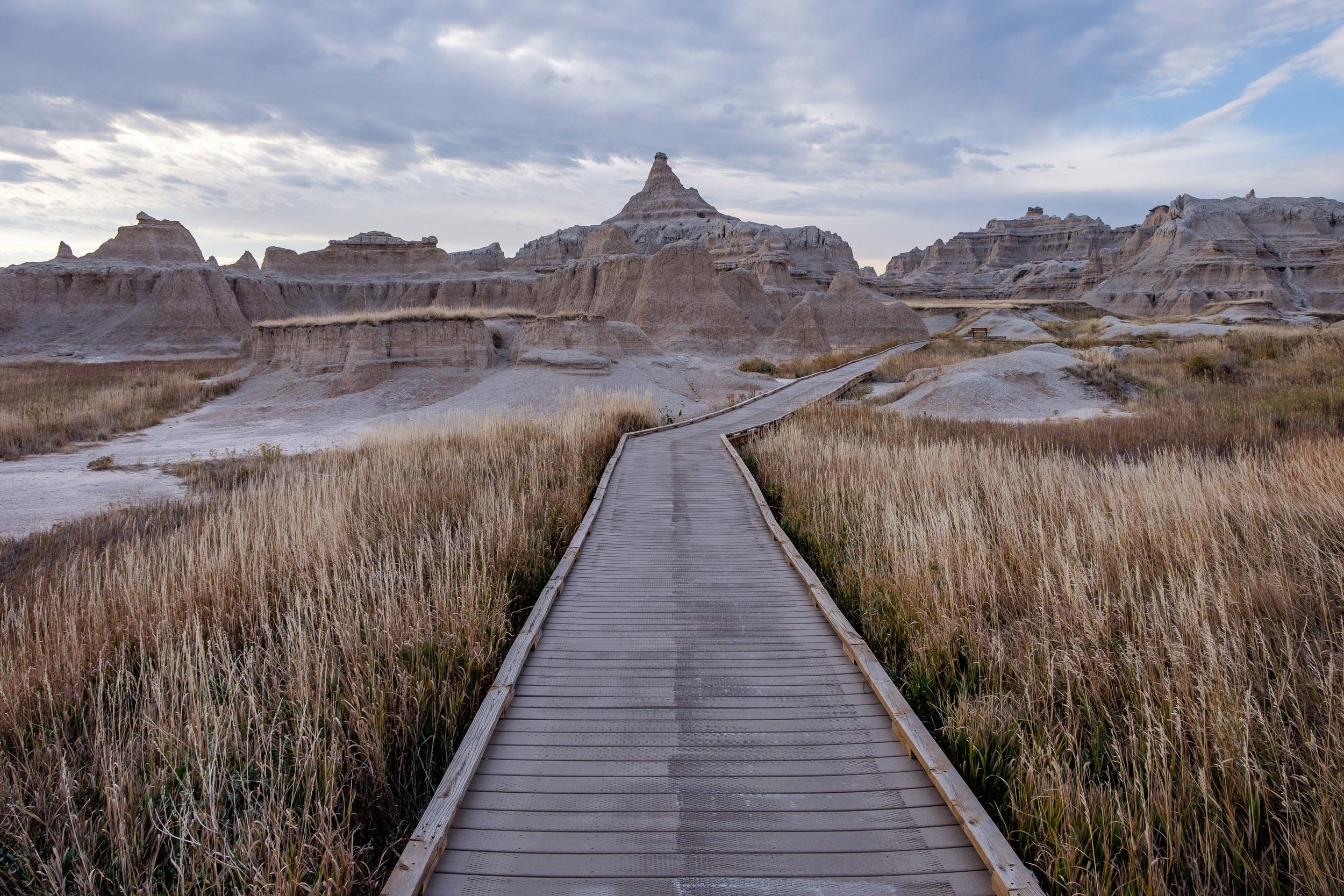 An elevated boardwalk on the Notch Trail traverses grasslands and badlands formations.