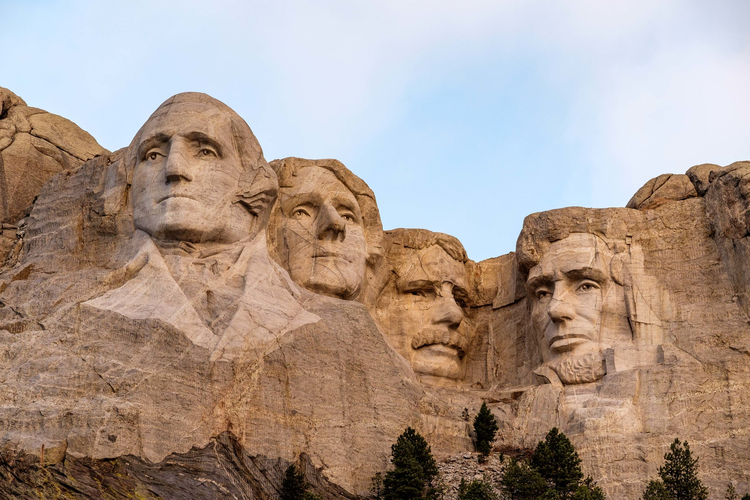 Mount Rushmore located 87 miles west of the Badlands depicts 60-ft. high granite carvings of Presidents George Washington, Thomas Jefferson, Theodore Roosevelt, and Abraham Lincoln.