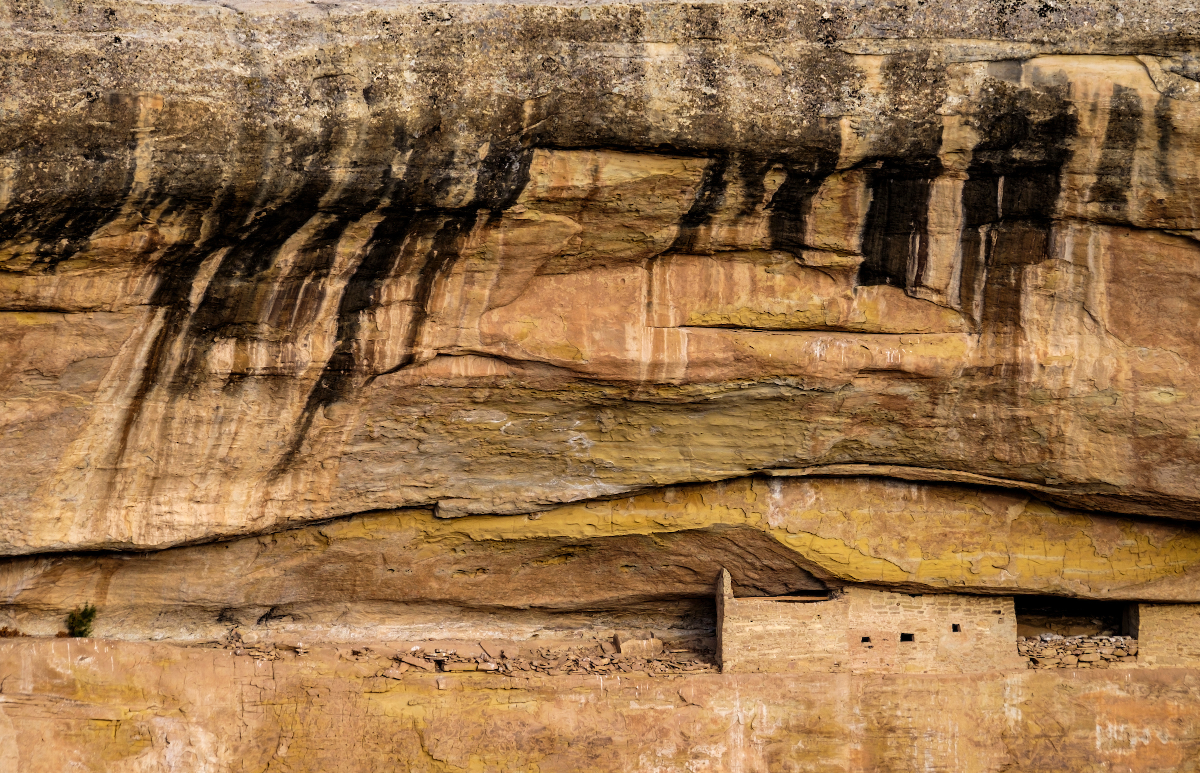Desert varnish (dark streaks on rock created by oxidization) as seen above a dwelling from a park road overlook.