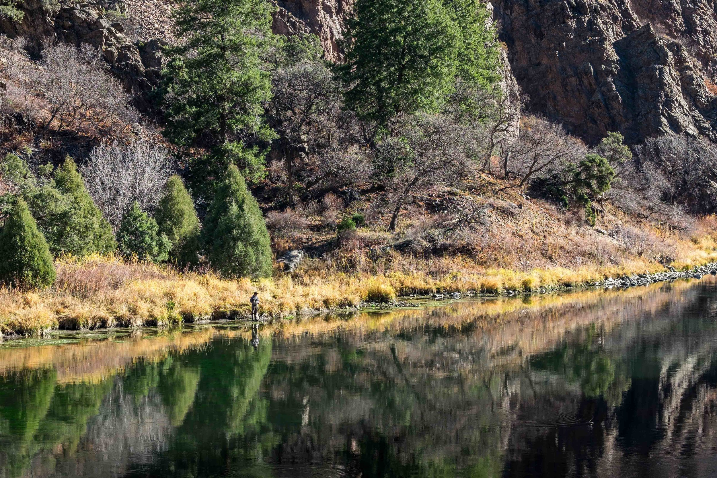 An angler drops a line into the Gunnison River at the bottom of the canyon in the  Curecanti National Recreation Area , also managed by the U.S. National Park Service.