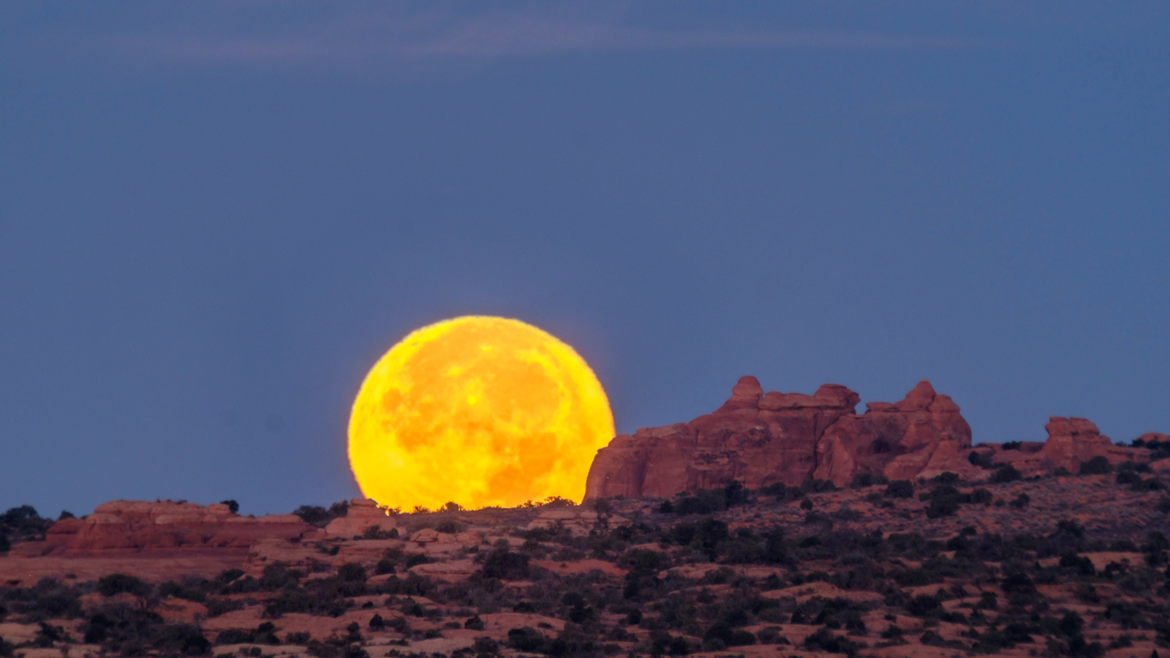 A November 2016 supermoon hugs the horizon in Arches National Park.