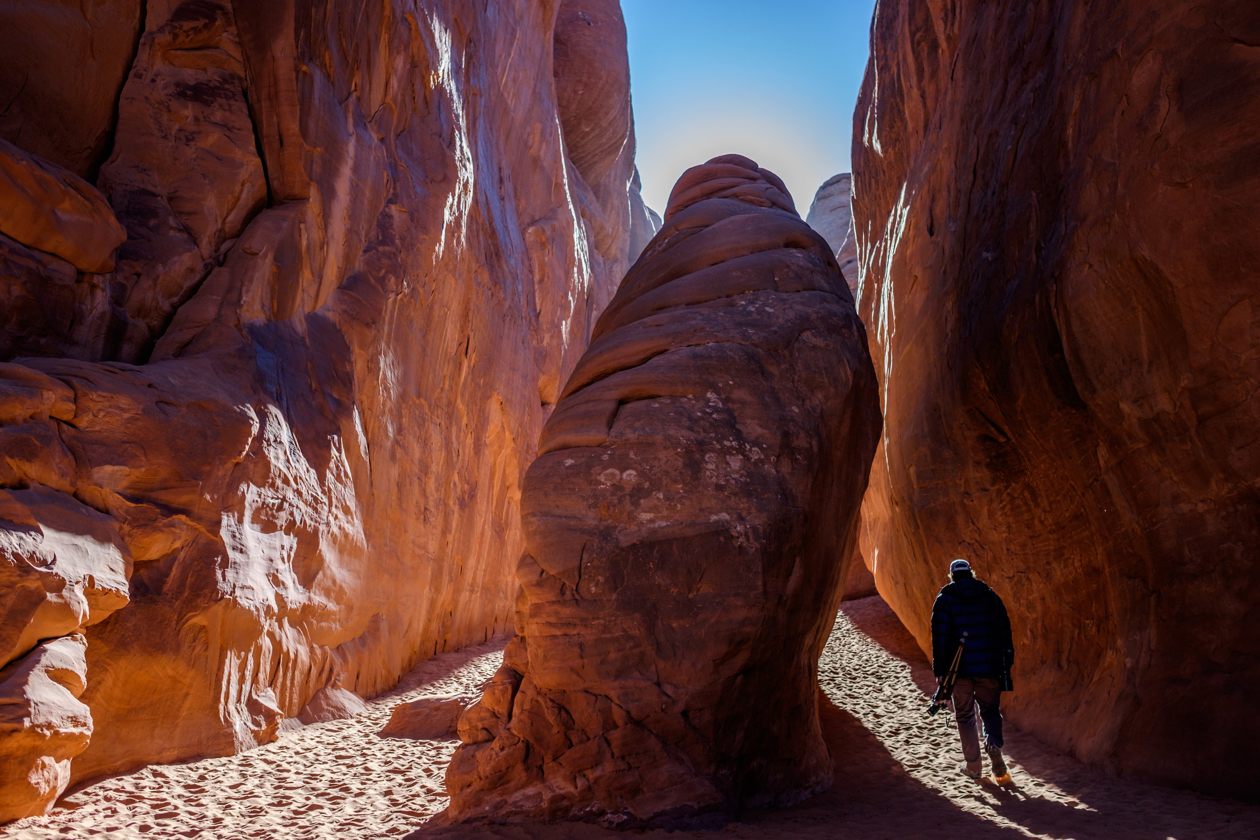 Jonathan walking inside of sandstone fins to Sand Dune Arch.
