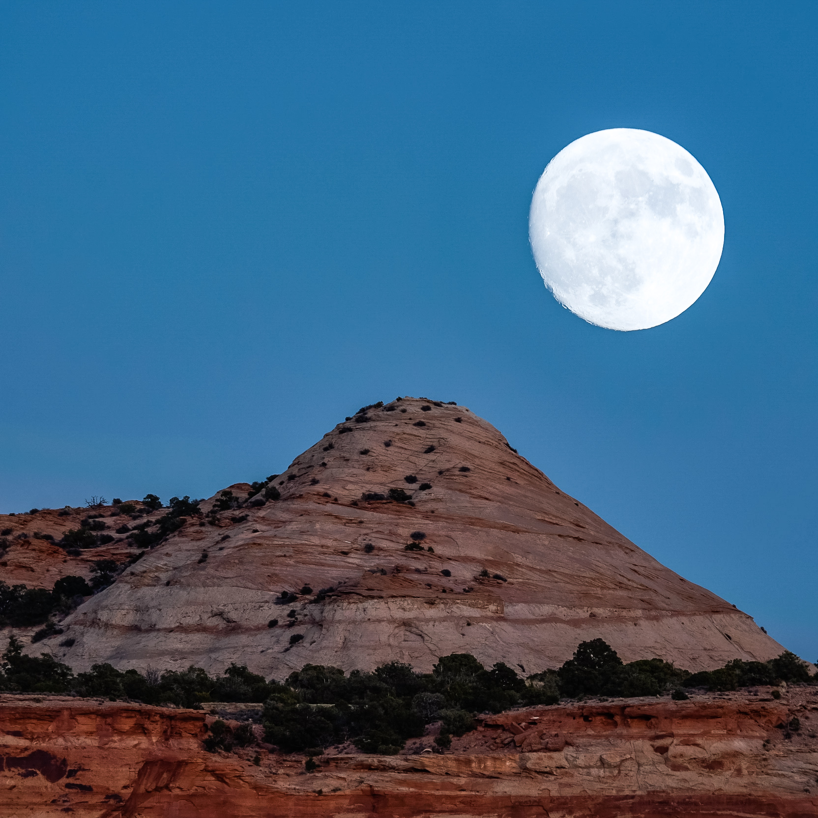 In-camera double exposure of a full moon rising over Canyonlands.