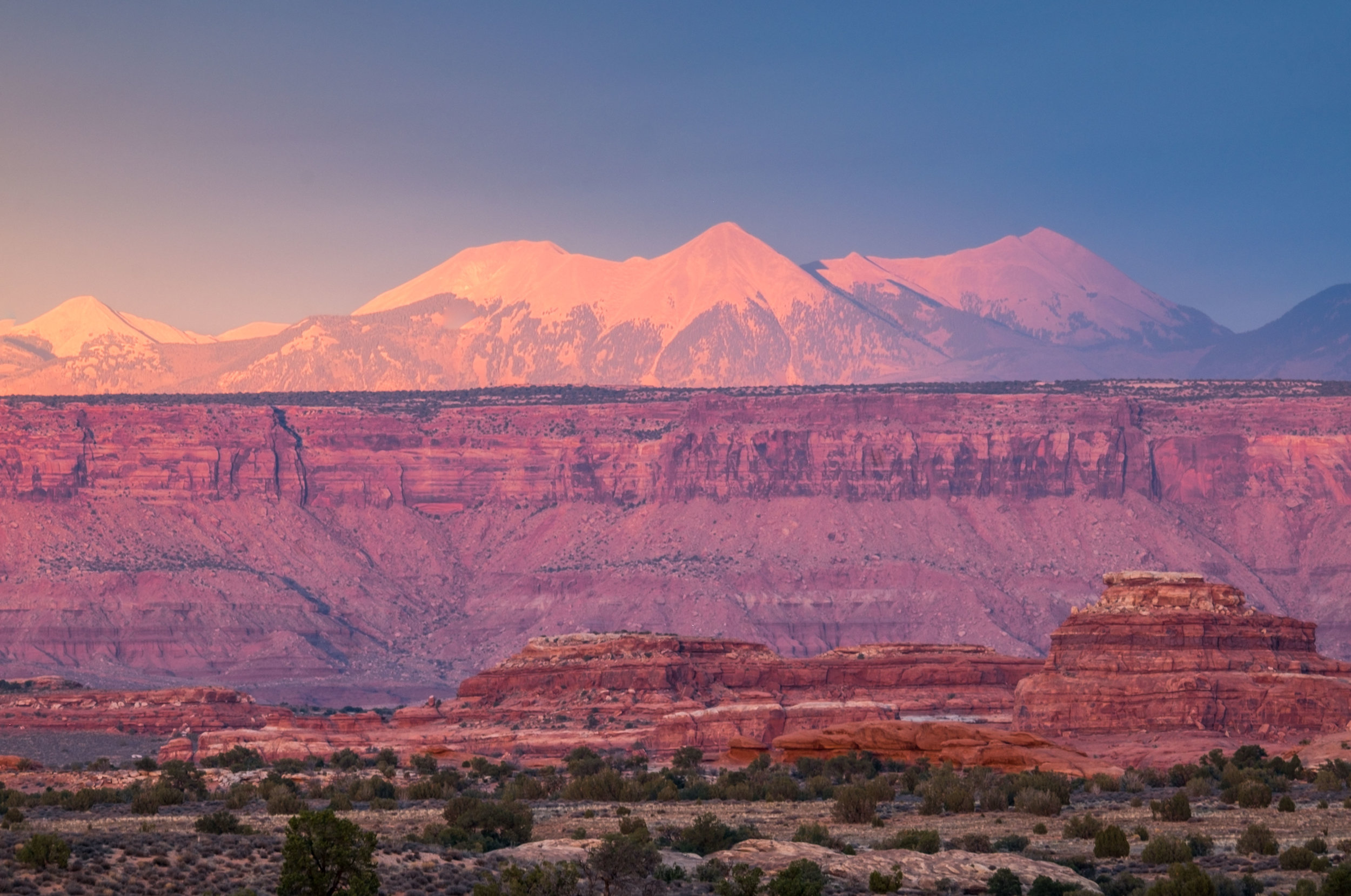The La Sal Mountains rise behind the Canyonlands illuminated by the light of a richly colored sunset.