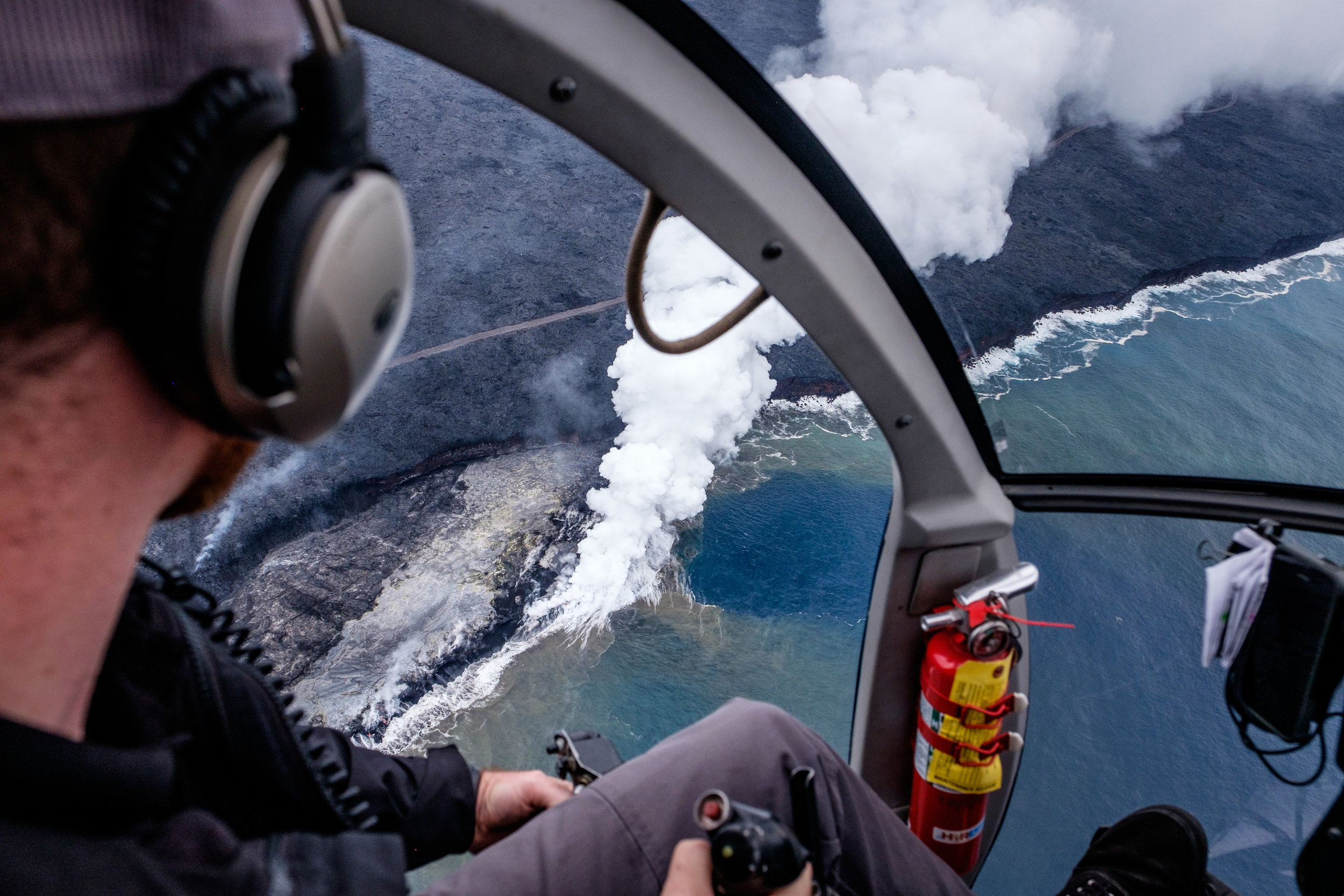 An amazing scene captured from an open-door helicopter while flying above where the Kīlauea volcano meets the largest ocean on Earth—the Pacific!