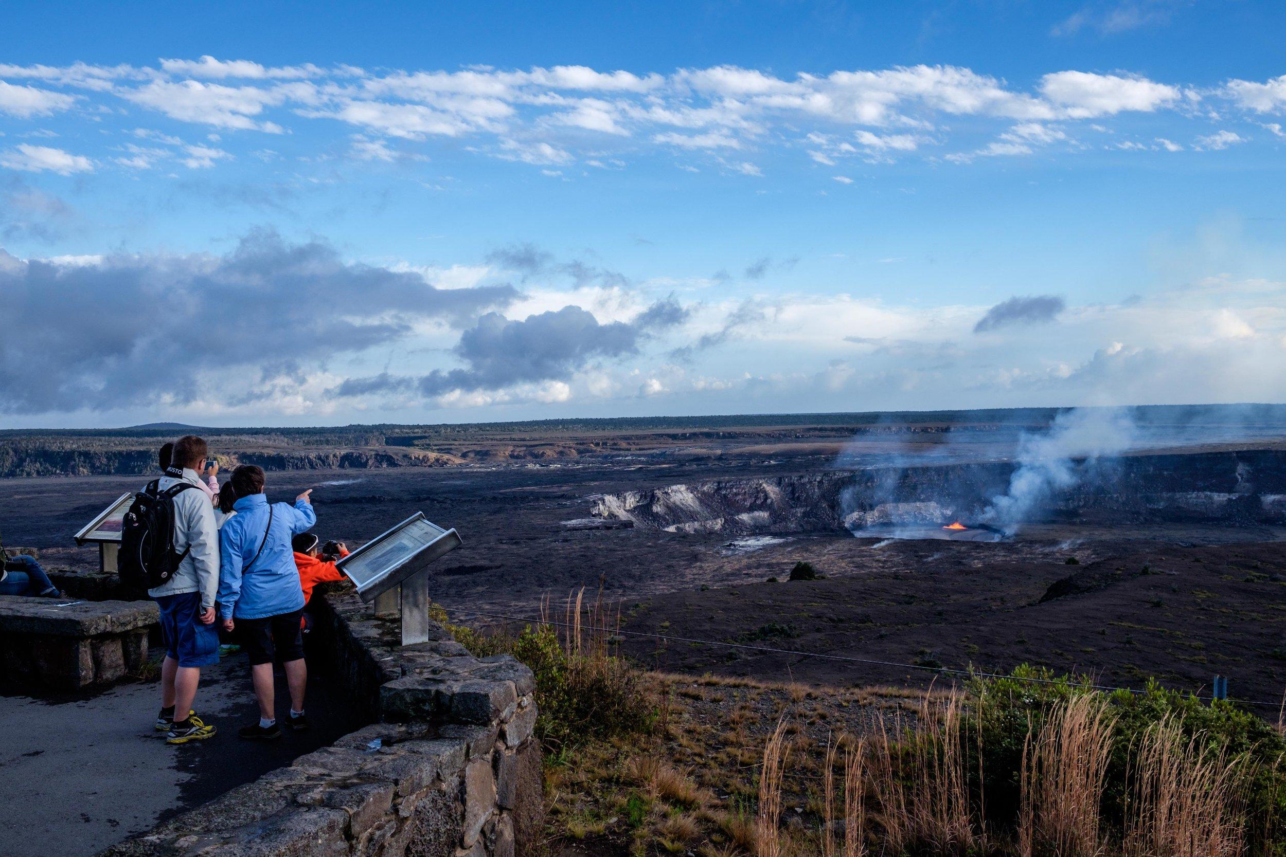 Hawai'i Volcanoes National Park visitors watch the wonder of the Halema'uma'u Crater erupting 100 feet away.