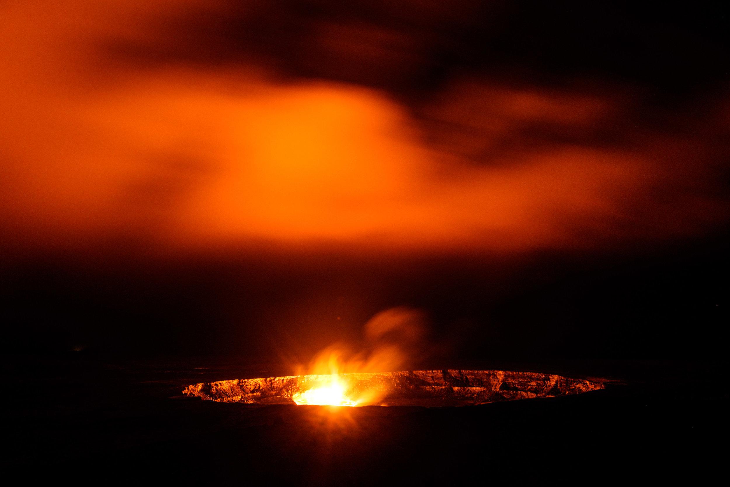 Lava lights up the black sky at night at the Halema'uma'u crater.