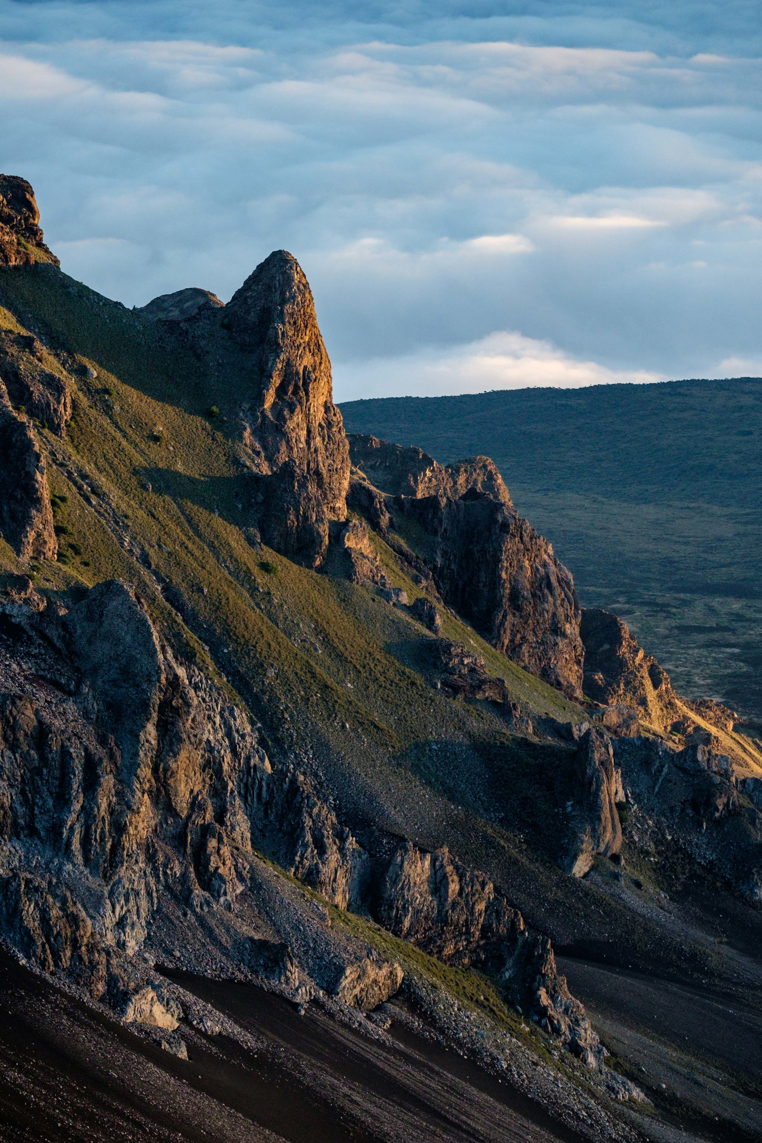 Distant rock formations along the crater rim, beautifully lit by the rising sun,.