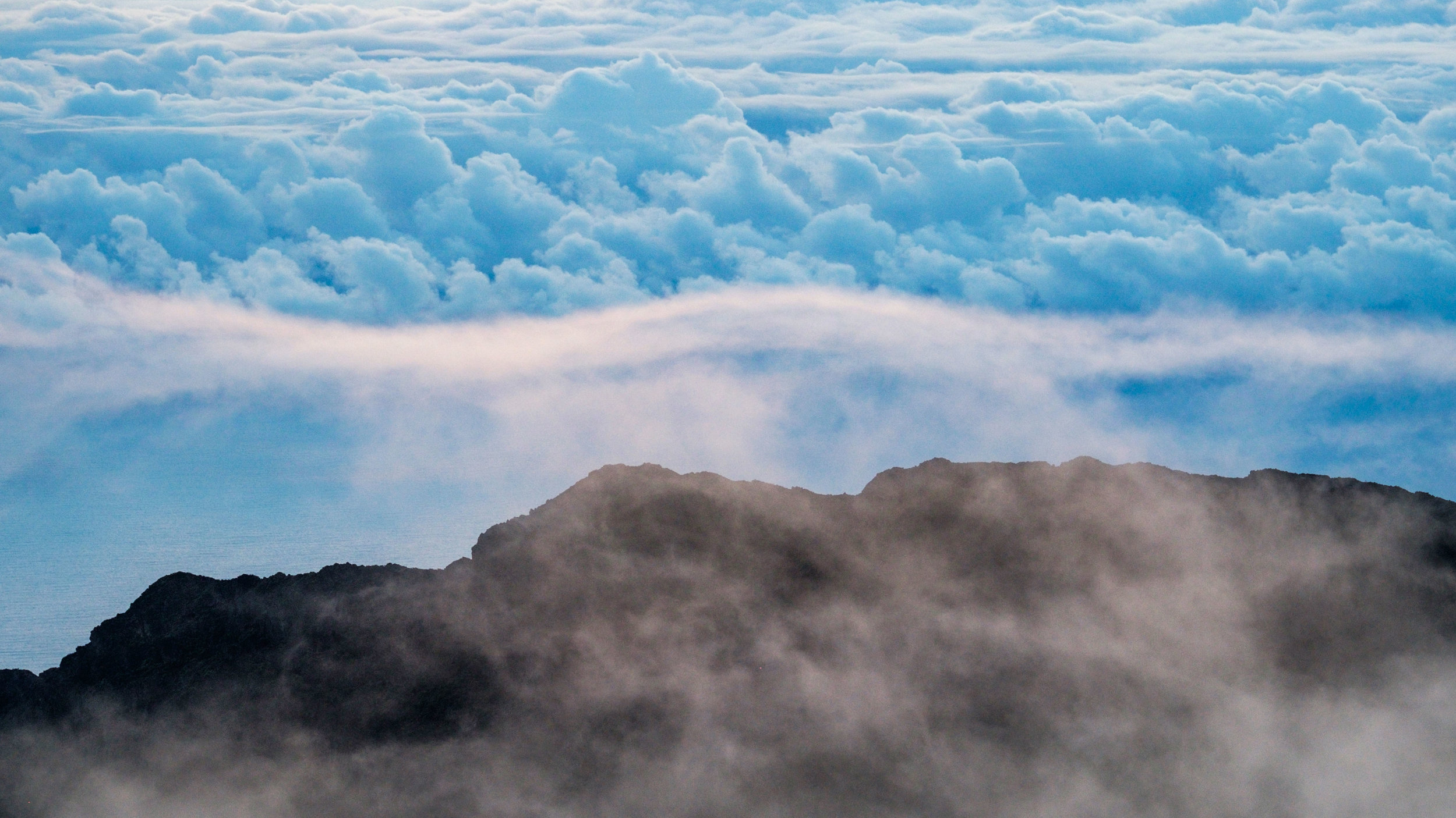Sunrise view of the clouds hugging the crater atop Haleakala summit in December, 2016.