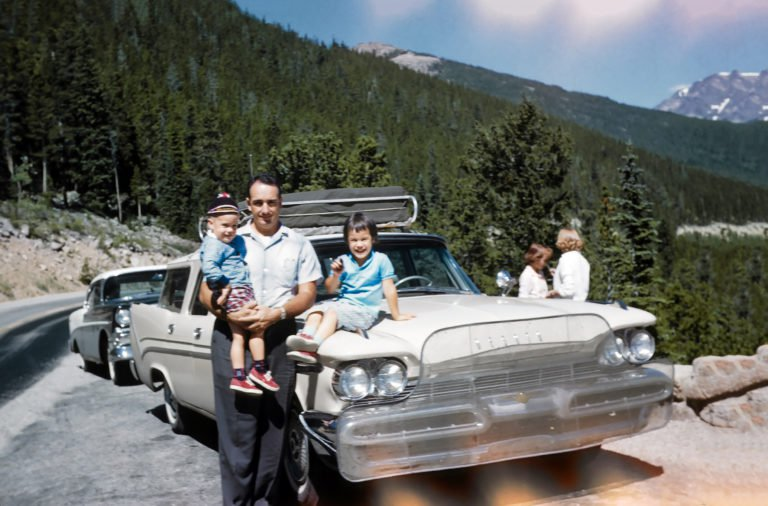 Nancy's Dad, Ernie Ward, holds David, as Ruthie sits on the hood with Peggy and Nancy in the background, during a family trip to Colorado in 1959. Ernie had the DeSoto station wagon outfitted with a bug guard and a roof rack.   COURTESY NANCY VAN GULICK/REMINISCE