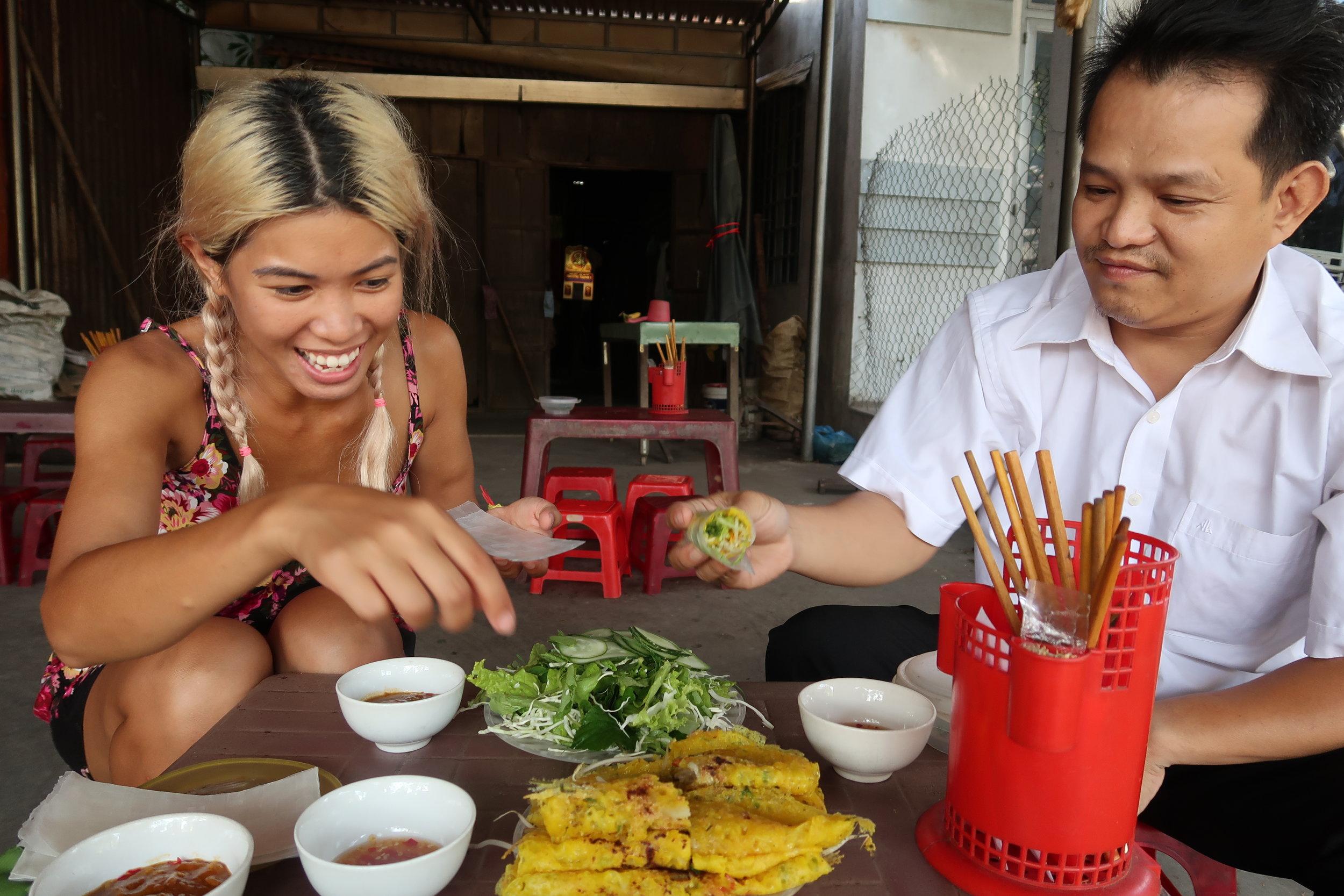Duong teaching us how banh xeo is eaten here