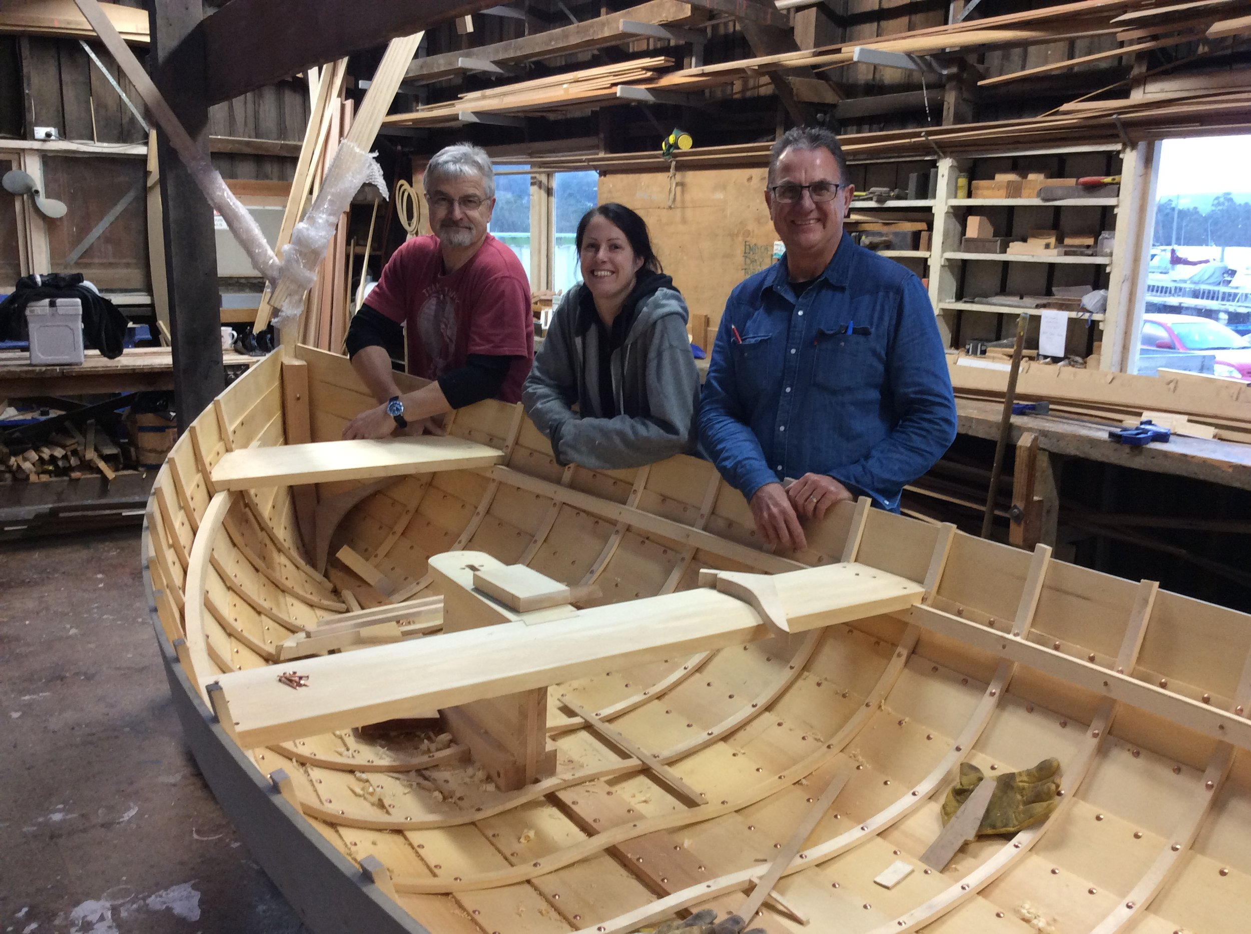 Mike Johnson with students Ellie and Wayne.  Wayne made the sailing version of the 11.4' dinghy to sell at the next Wooden Boat Festival.