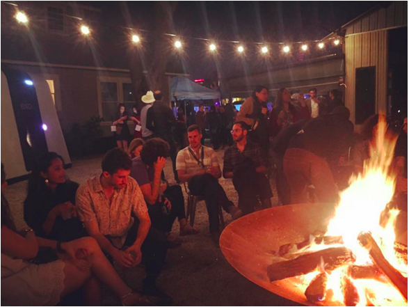 People gathered by the fire at night