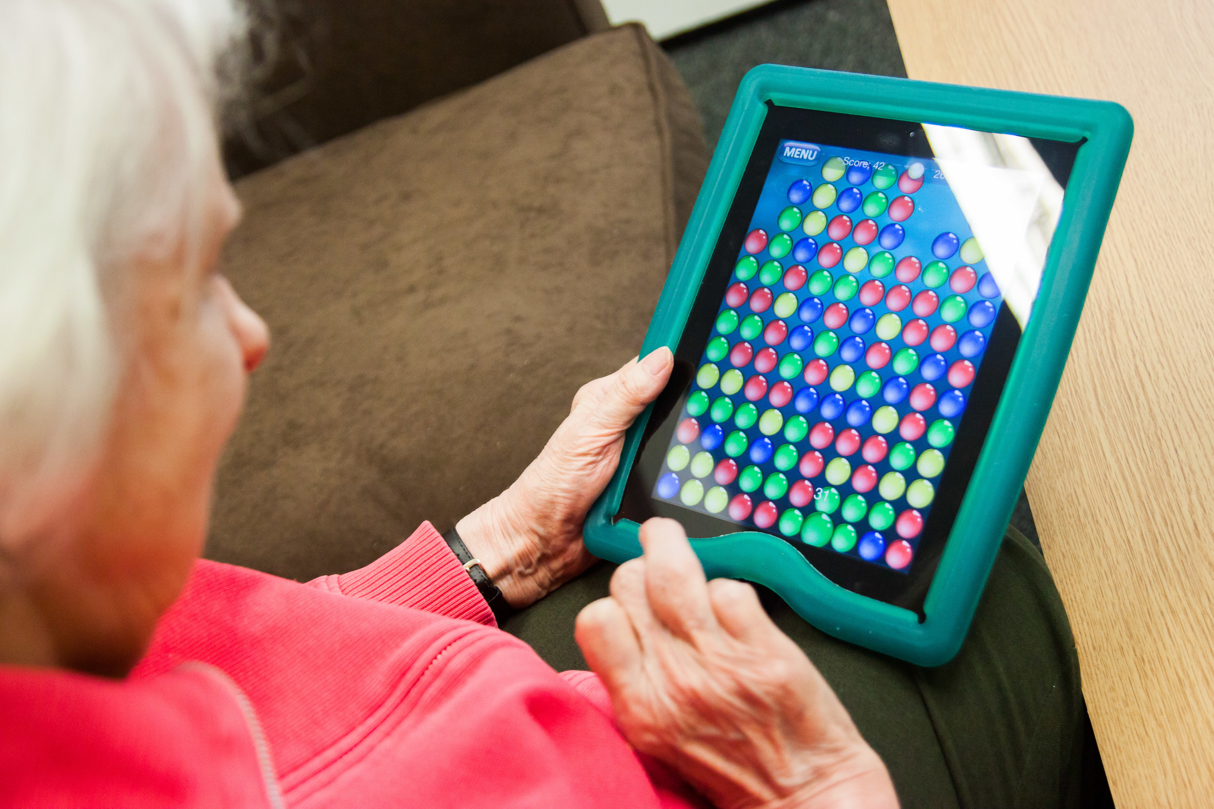 A woman enjoying Bubble Explode, one of the games identified through the AcTo Dementia project
