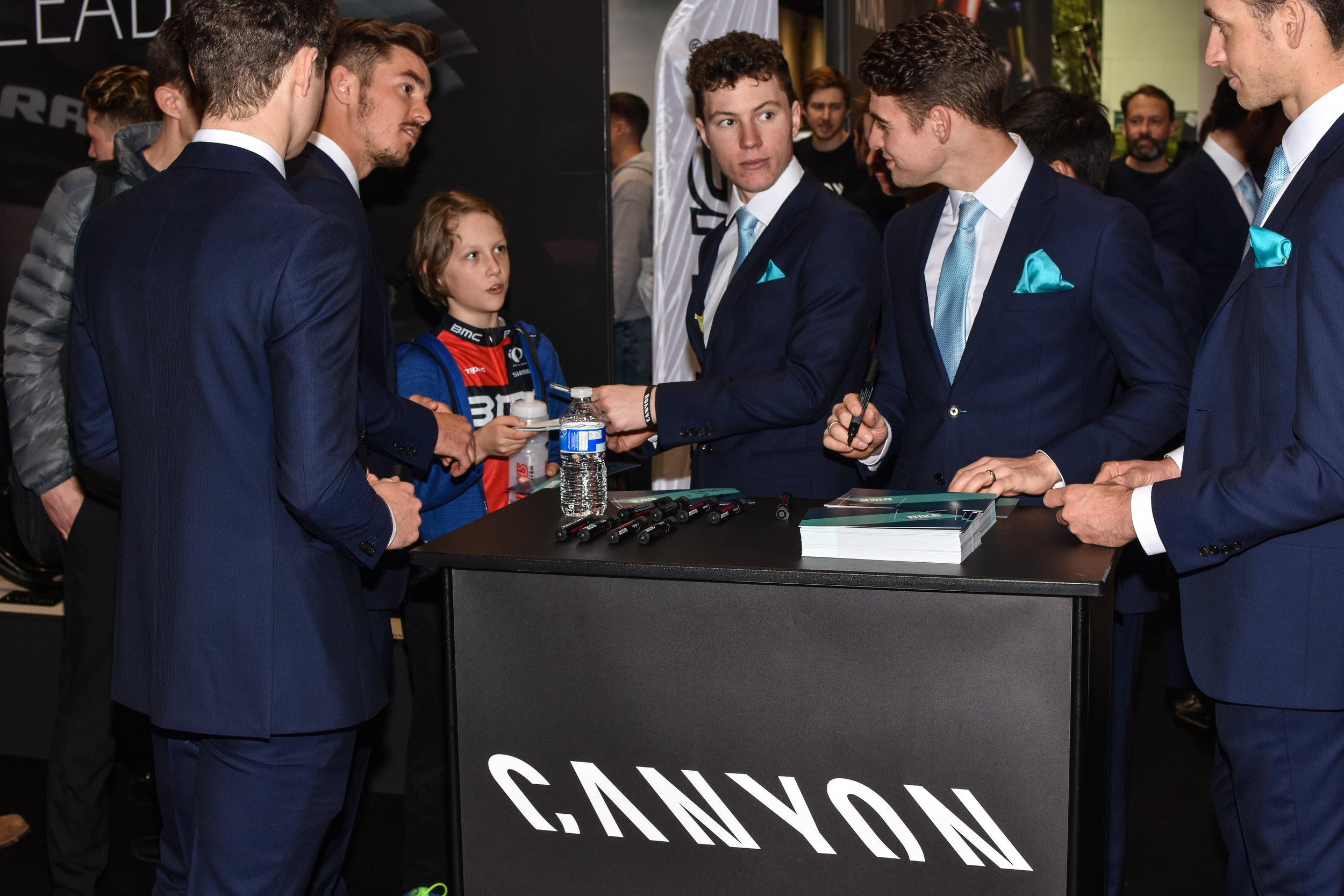 A young cyclist asking for an autograph from the team