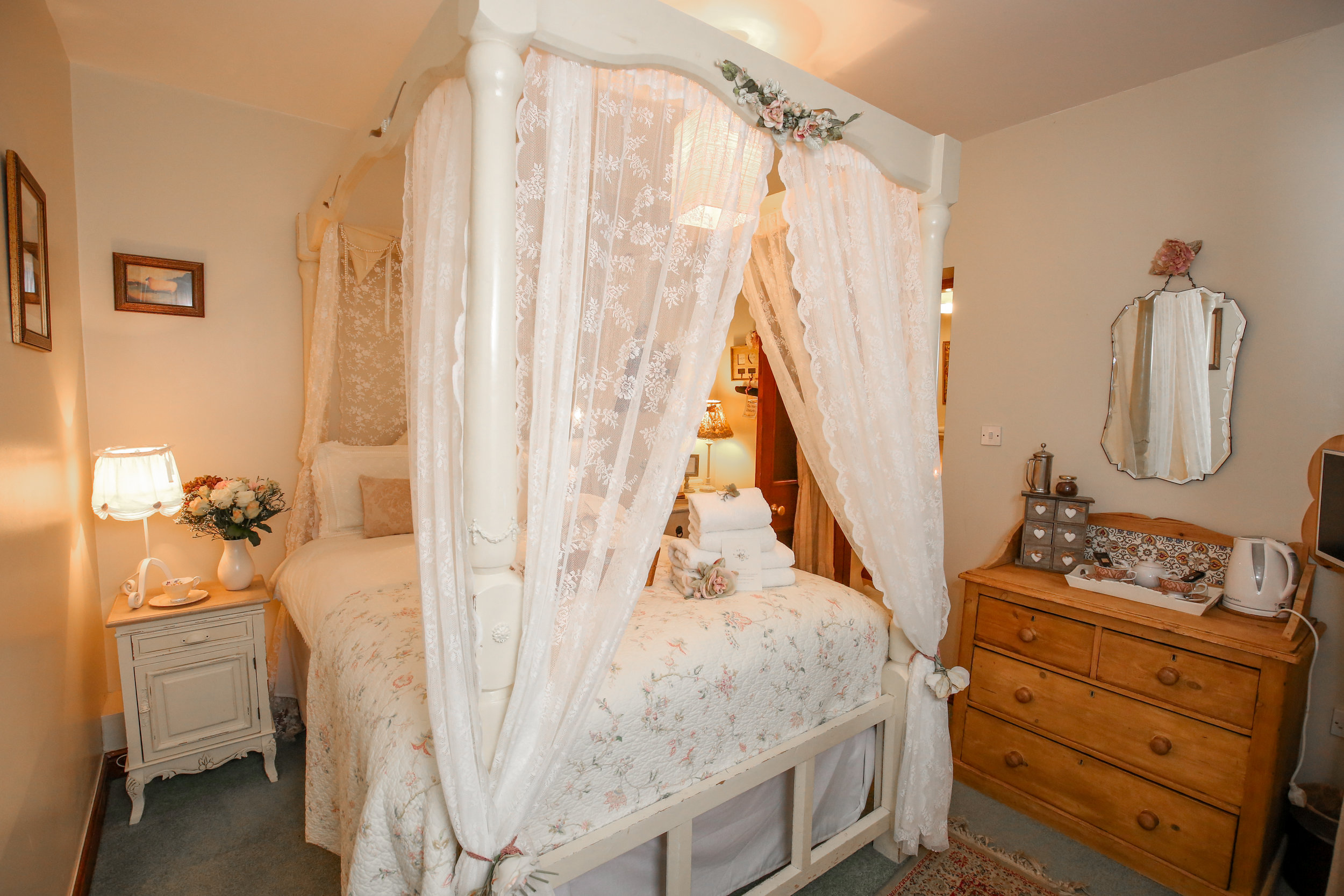 Room 2 - Room 2 is a warm and welcoming accessible double on the ground floor. Romantic lace drapes envelope the white four poster bed, and it features an en-suite shower. It's decked front is shared with Room 1 and provides the perfect spot to enjoy our historic courtyard garden.