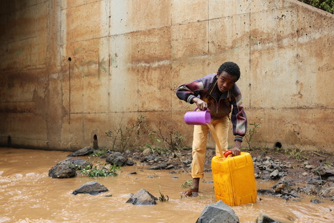 Gobena collects muddy river water for his family. Image by WaterAid/ Behailu Shiferaw
