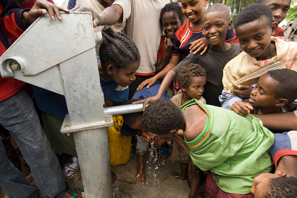 community members drinking from new water tap,charity: water