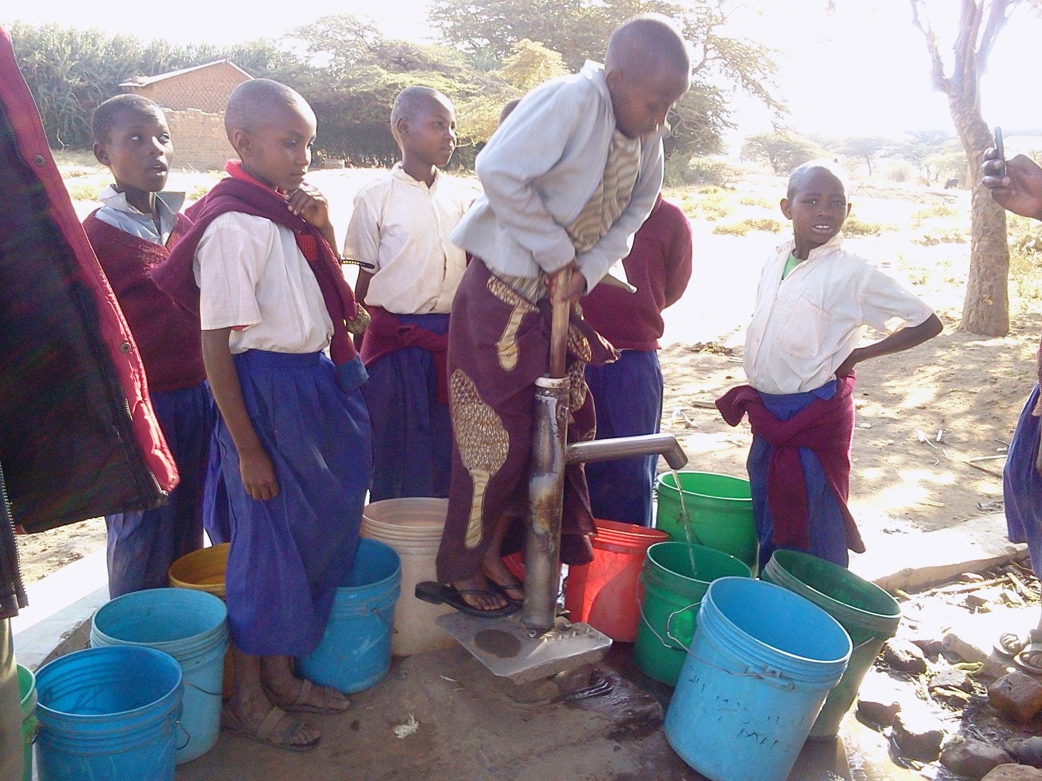 Children using the new water pump, WaterAid