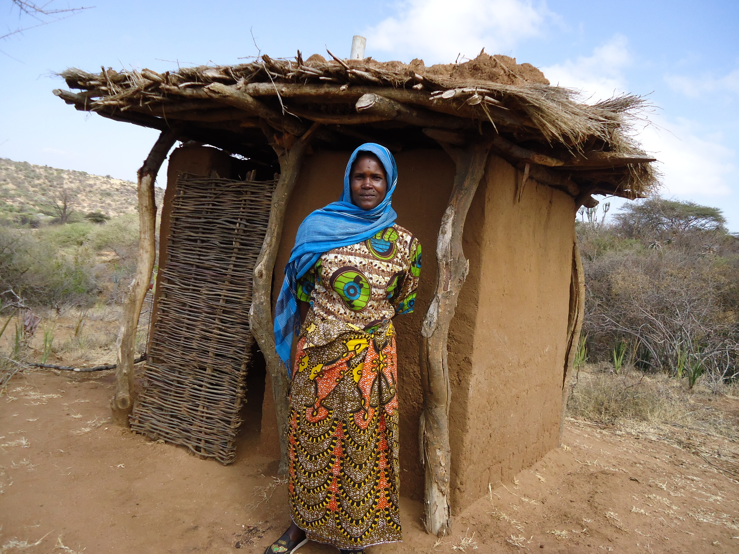 Woman standing outside her new toilet, WaterAid