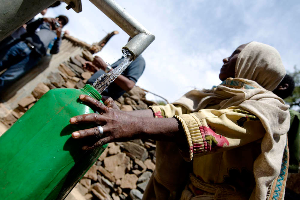 woman filling a canteen with clean water, charity: water