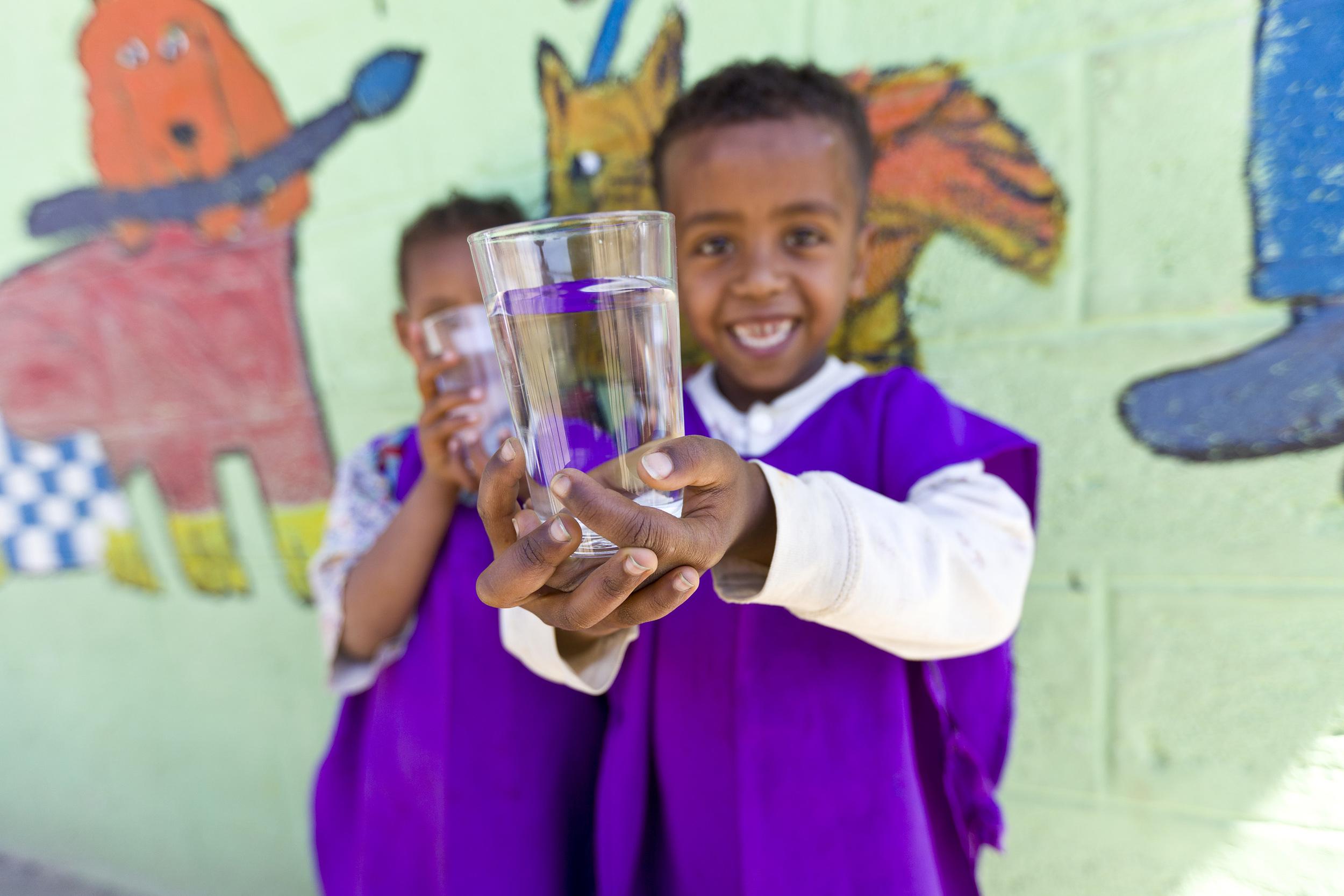 children in an orphanage enjoying filtered drinking water, splash