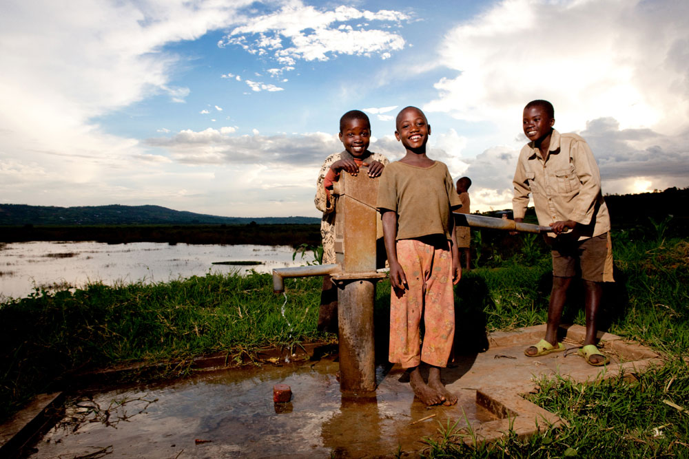 Children enjoying new water pump, charity: water